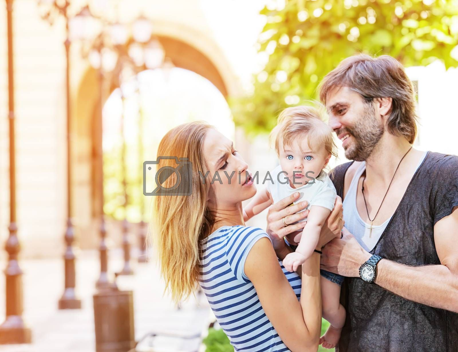 A young family couple with their cute little baby boy outdoors.