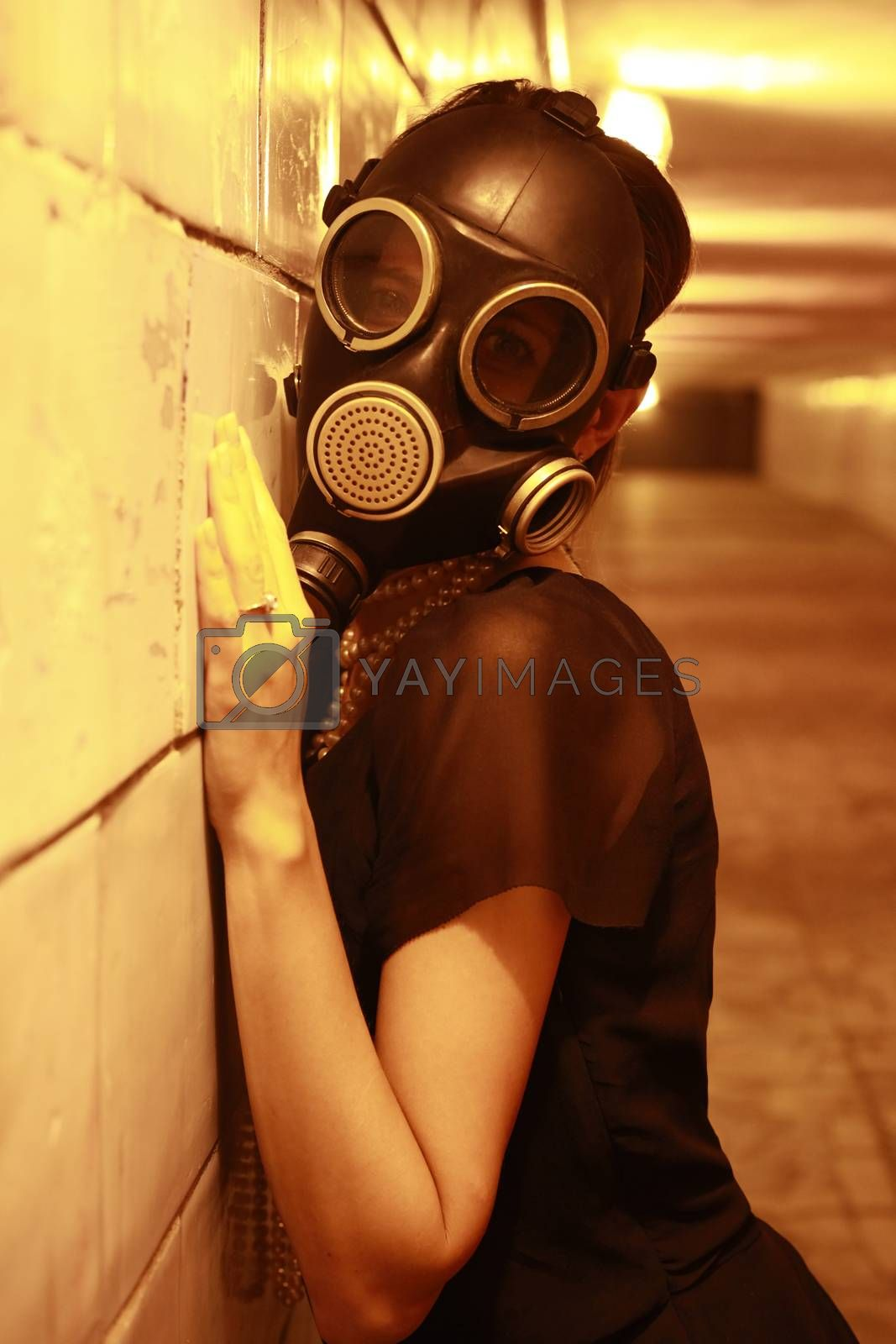 Woman in a gas mask in the night tunnel