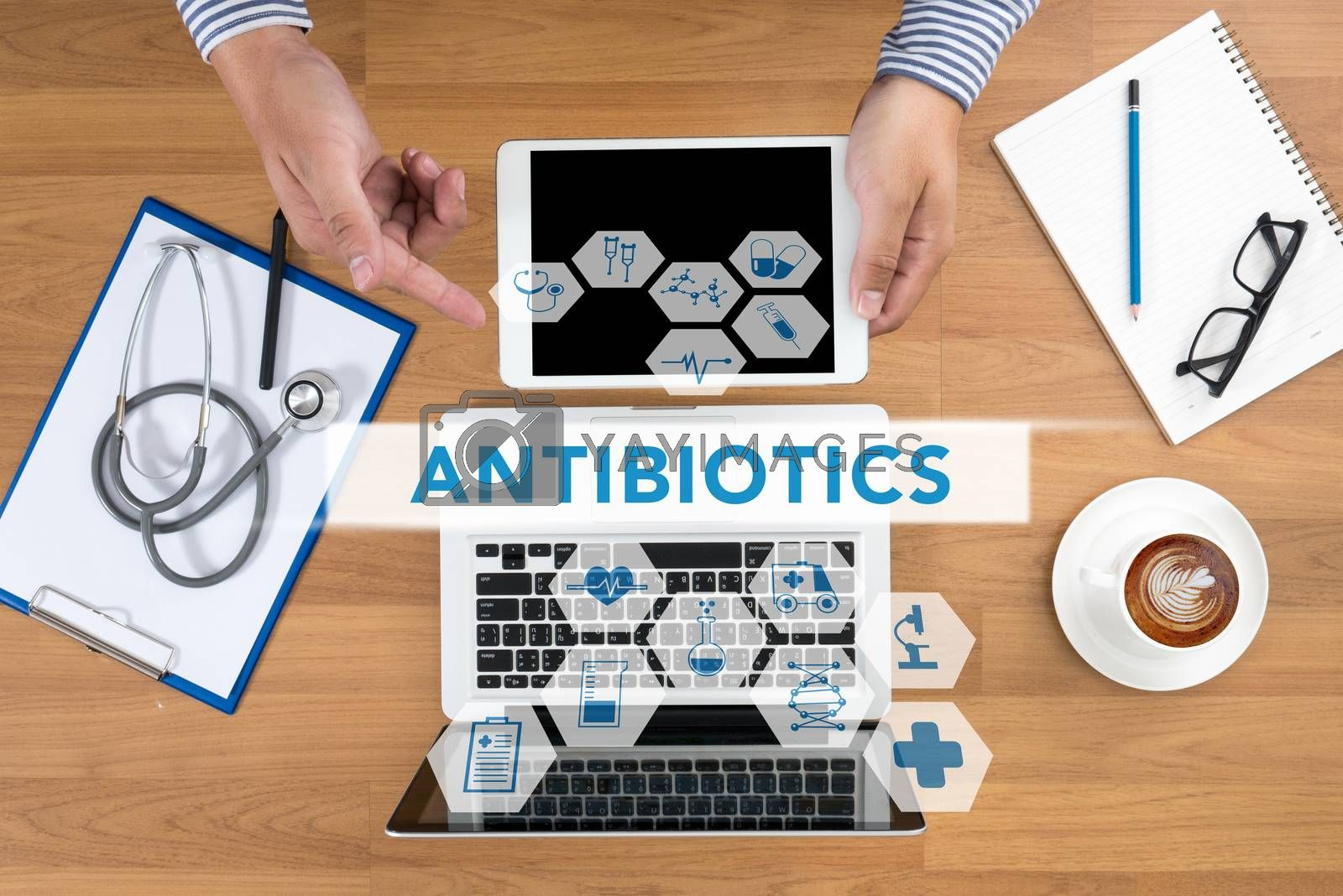 ANTIBIOTICS CONCEPT Doctor touch digital tablet, desktop with medical equipment on background, top view, coffee