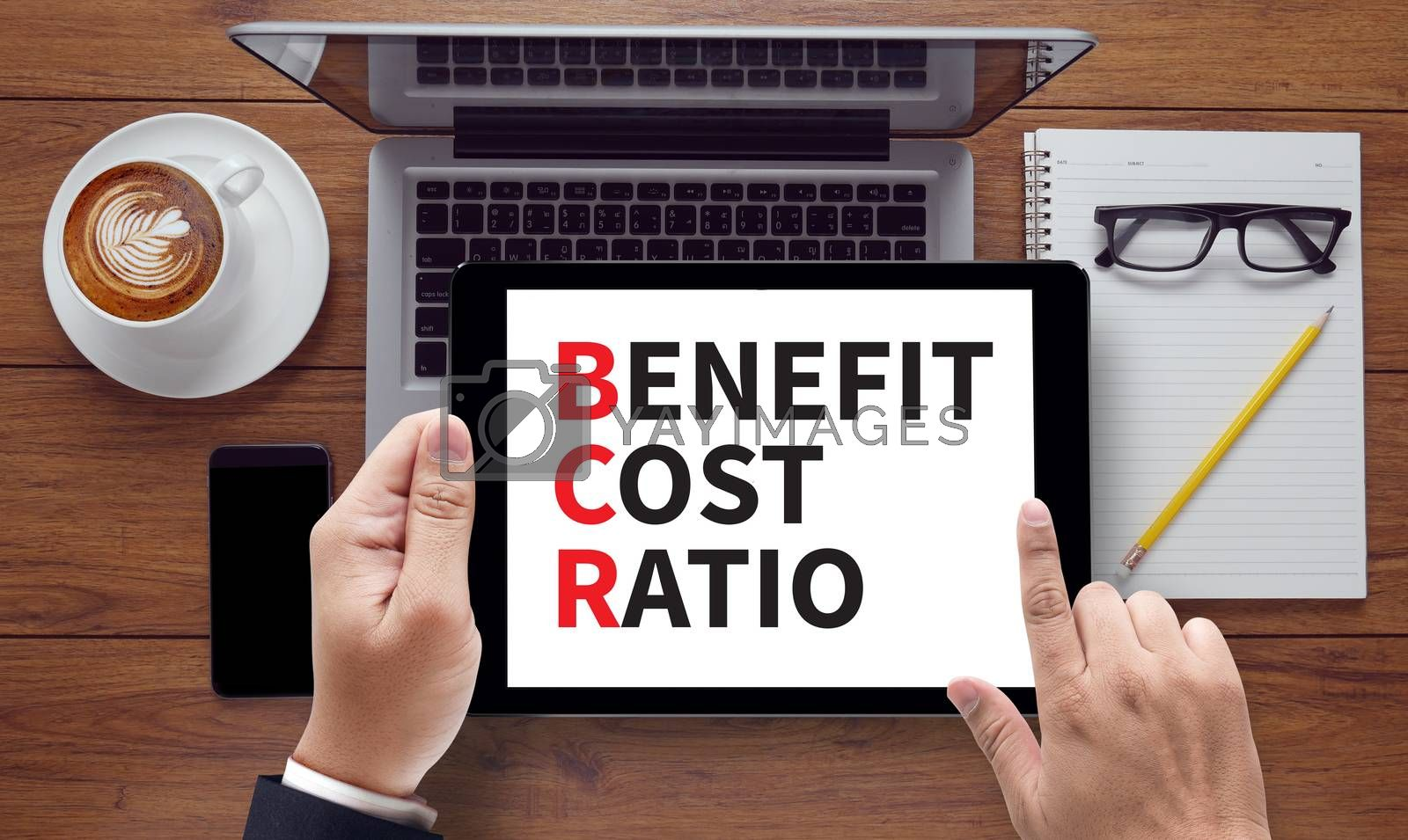 BENEFIT COST RATIO, on the tablet pc screen held by businessman hands - online, top view
