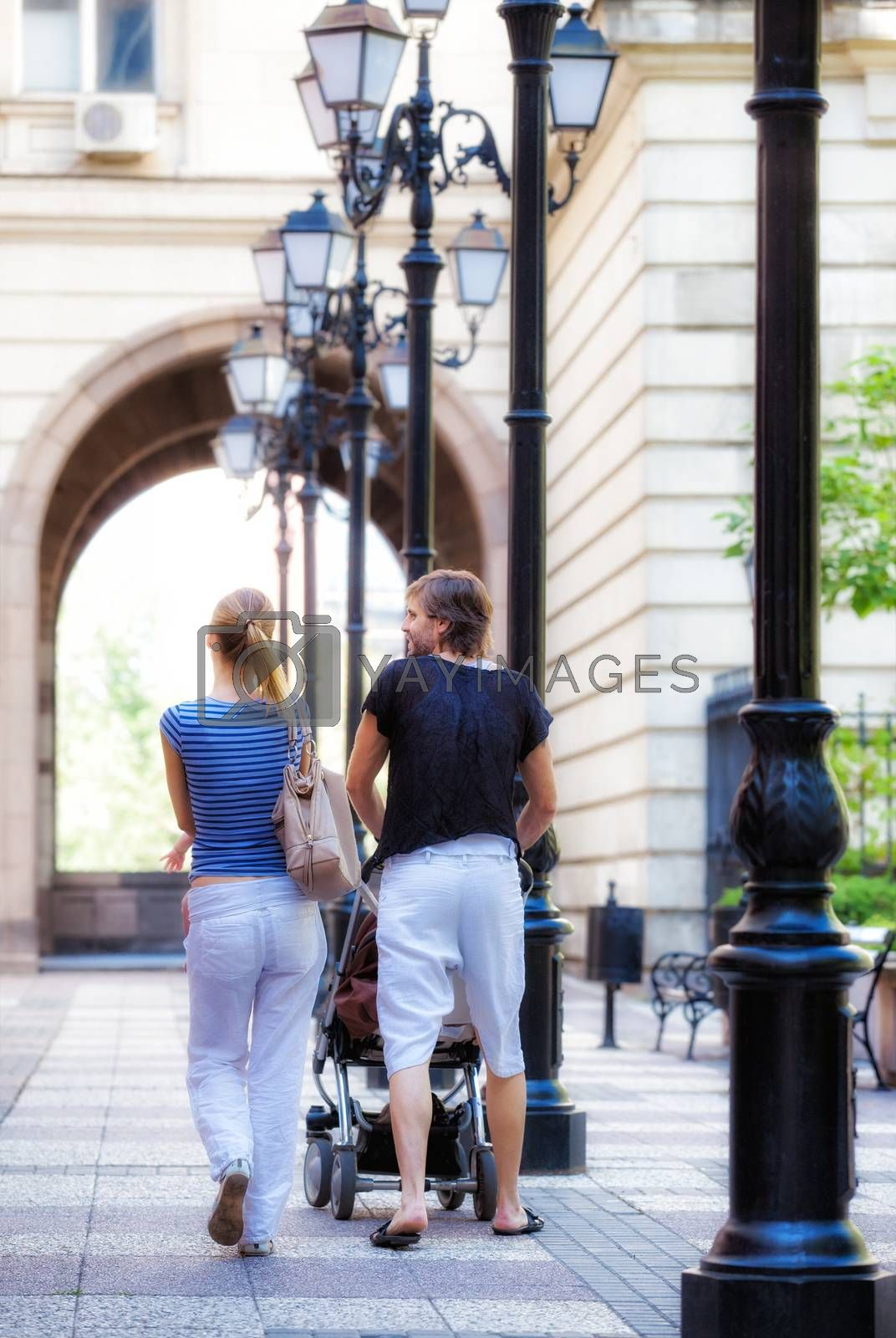 A view of a young couple with a baby walking away downtown in a sunny summer or spring day.