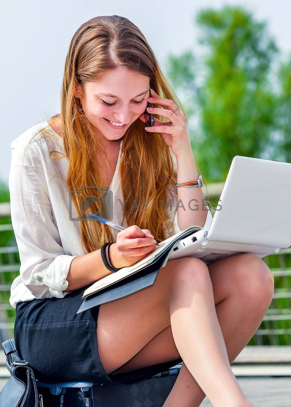dynamic young executive girl on the phone taking notes on her agenda. Symbolizing a job search or a trade of outsourcing