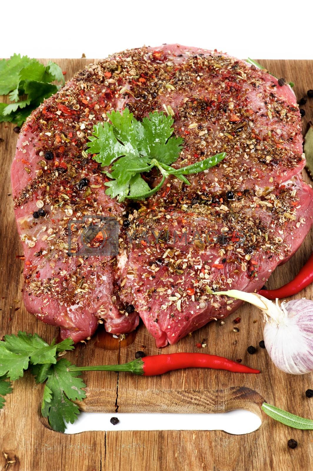Marinated Raw Boneless Beef Shank with Herbs and Spices, Garlic and Chili Pepper closeup on Wooden Cutting Board on Cross Section on White background