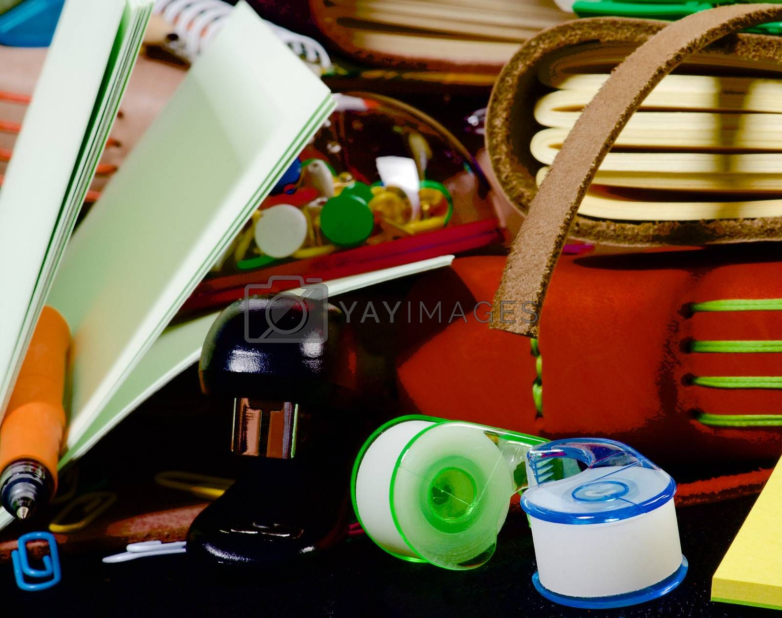 Background of Stationery Items with Notepads, Pens, Pencils, Paper Clips, Tape Dispenser, Marker and Stapler closeup