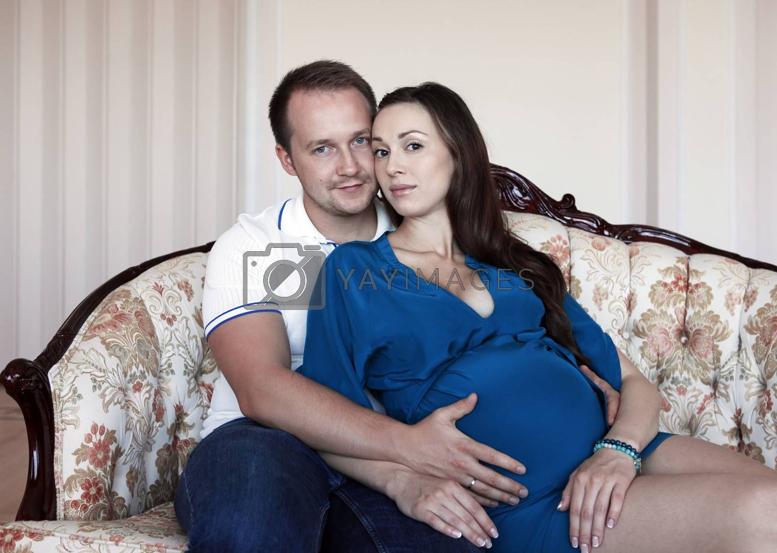 Happy beautiful pregnant woman with his husband at home