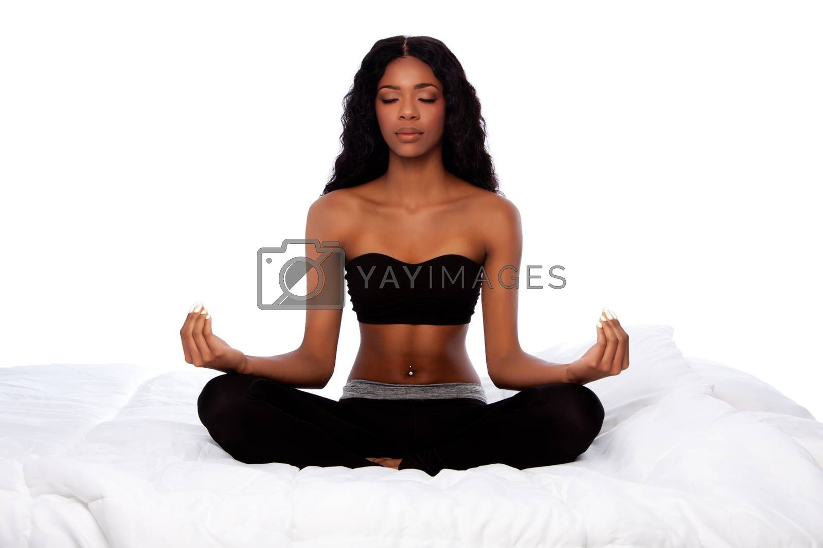 Beautiful african woman sitting in lotus yoga pose on soft fluffy white bed.
