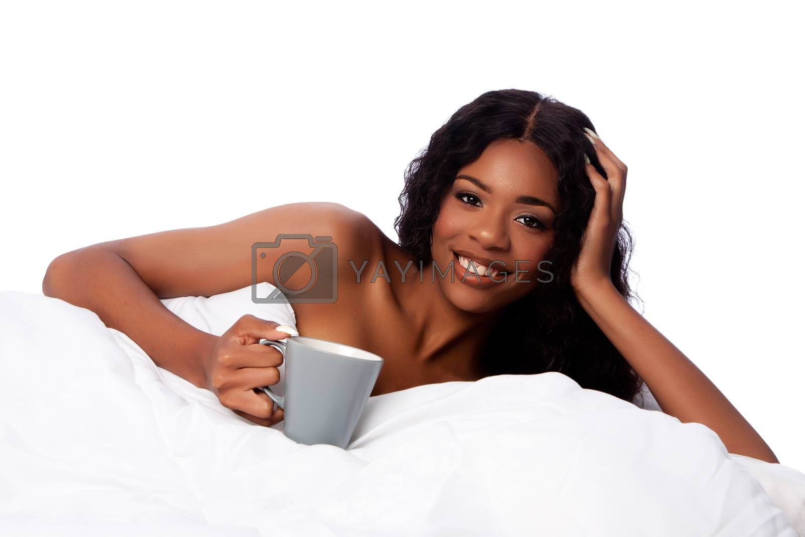 Beautiful happy smiling african woman in white bed waking up with coffee or tea after a deep sleep.