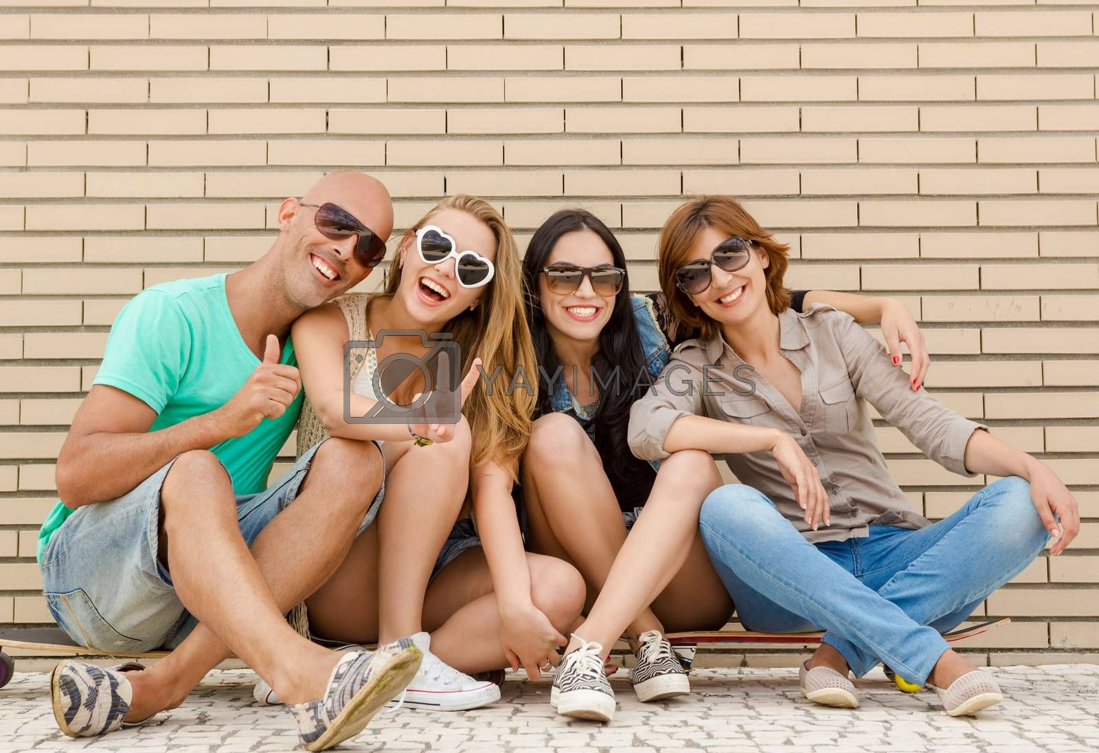 Group of friends posing in front of a brick wall