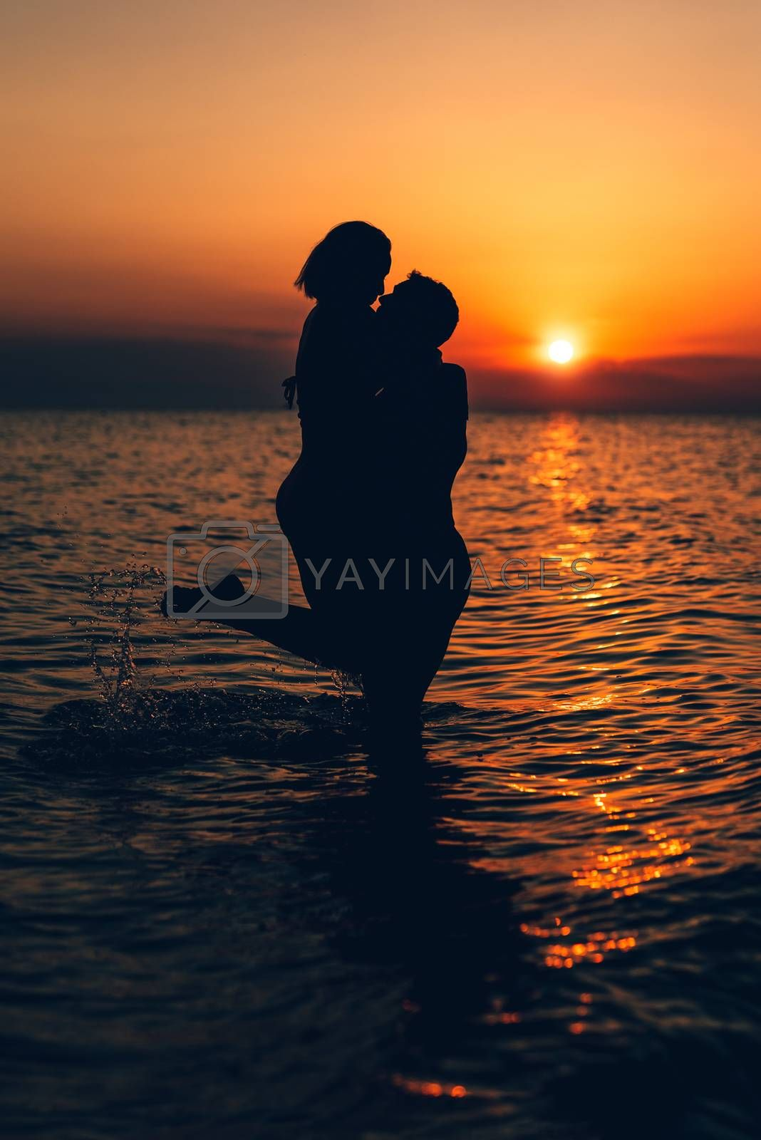 Silhouette of a loving couple hugging and kissing at sunset on the beach.