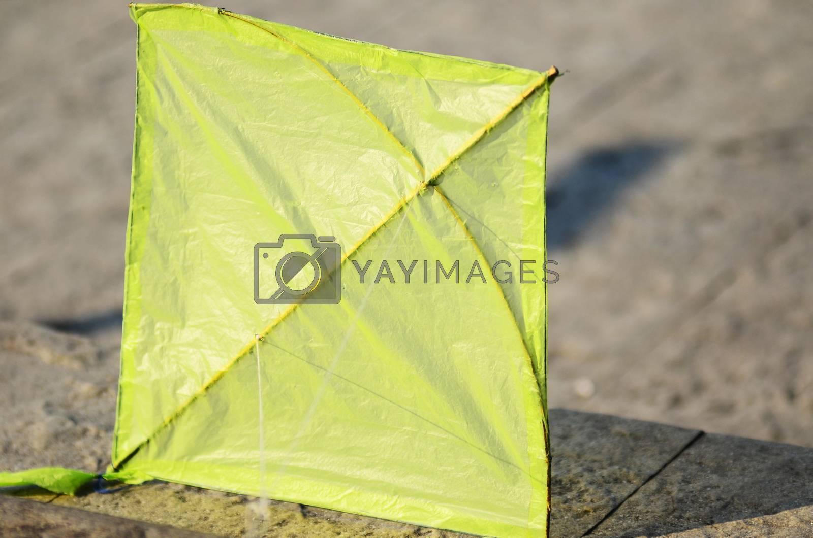 Green kite on concrete floor not flying
