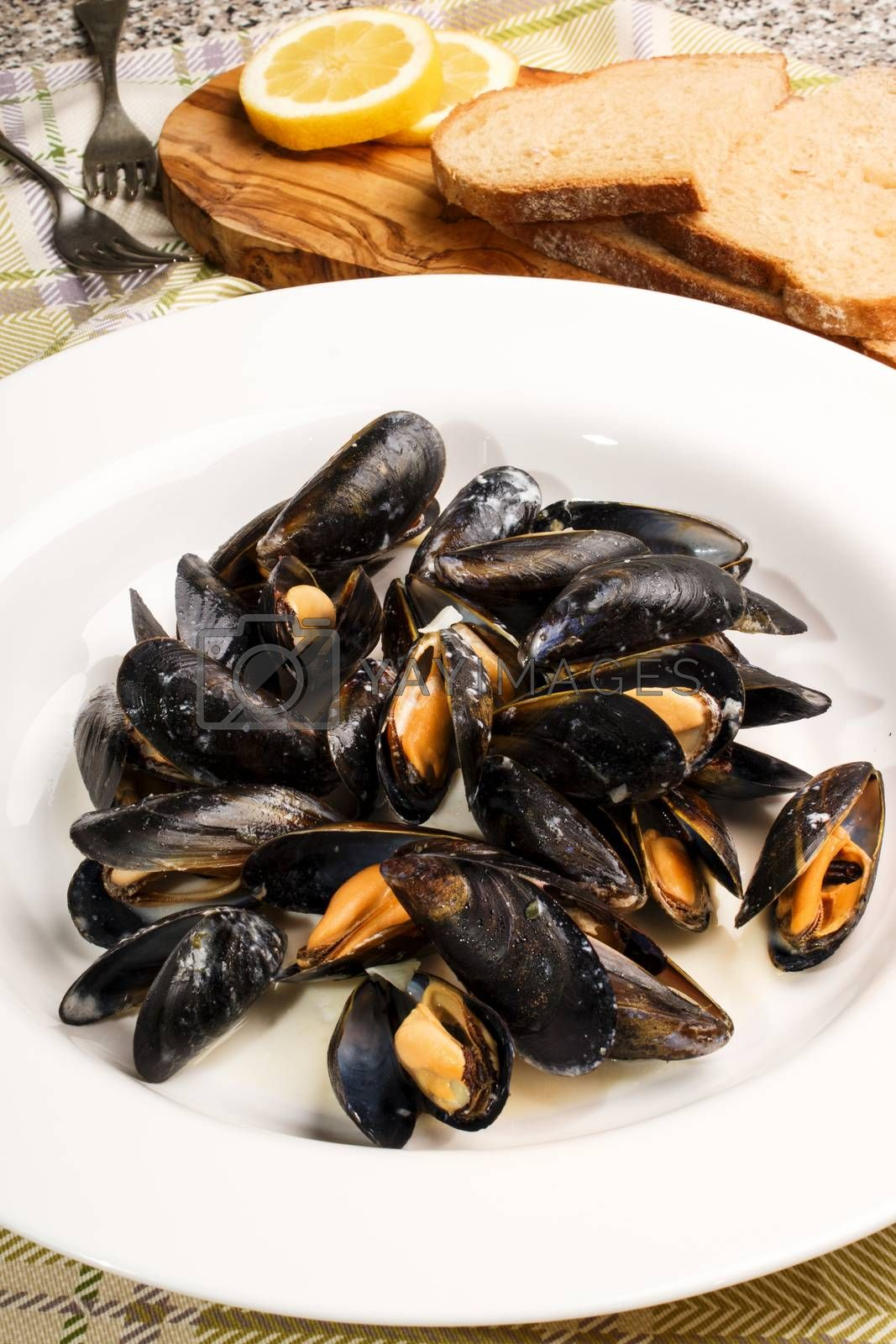 mussels with garlic and butter sauce in a deep plate with bread and slice lemon