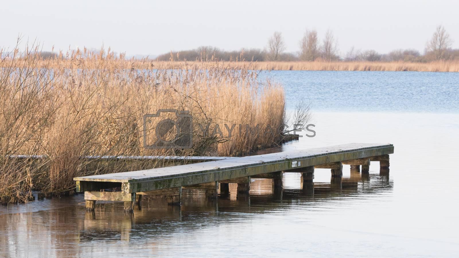 Long wooden jetty at lake at cold winter day