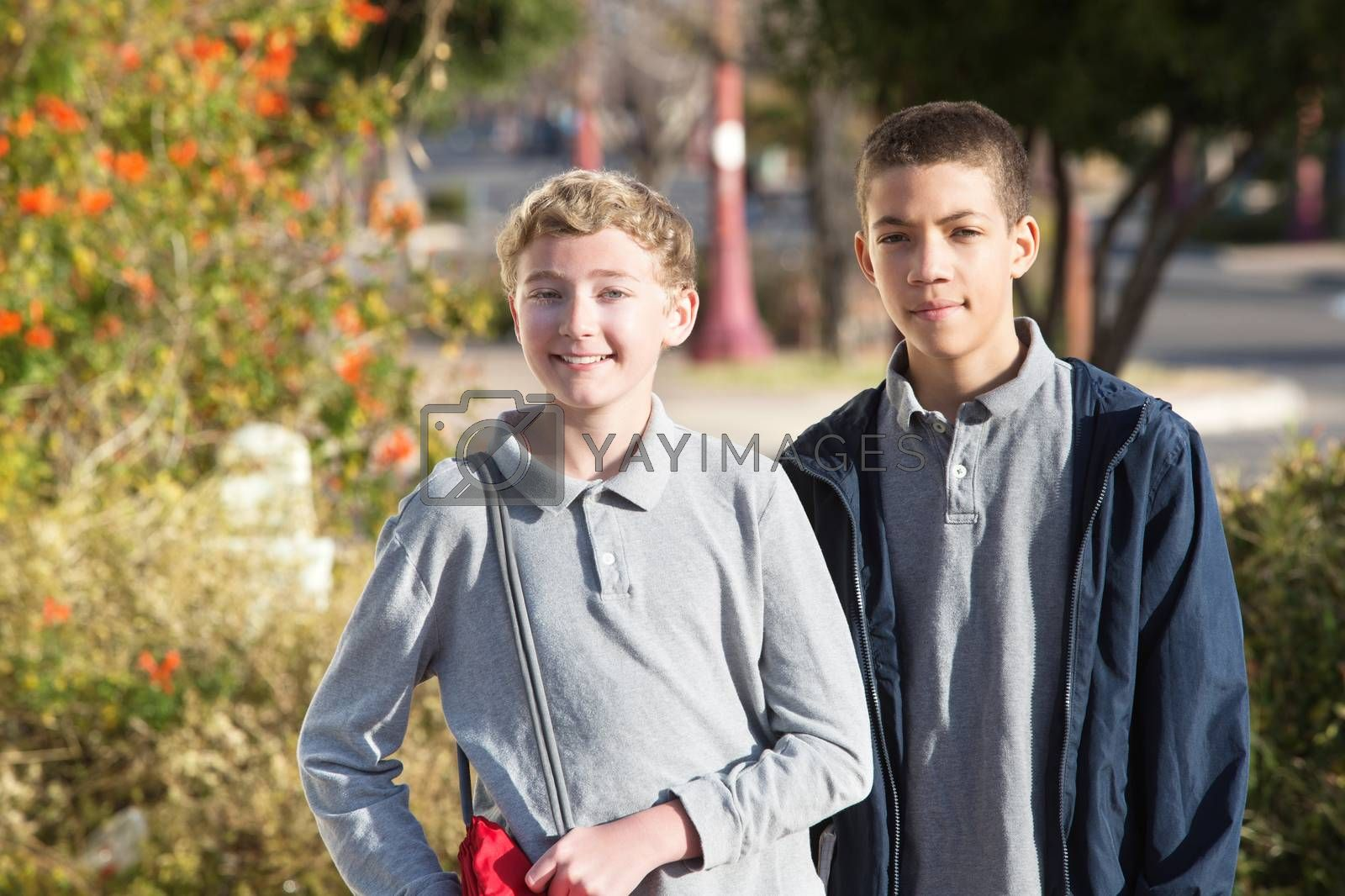 Pair of teen male students standing outside during spring season