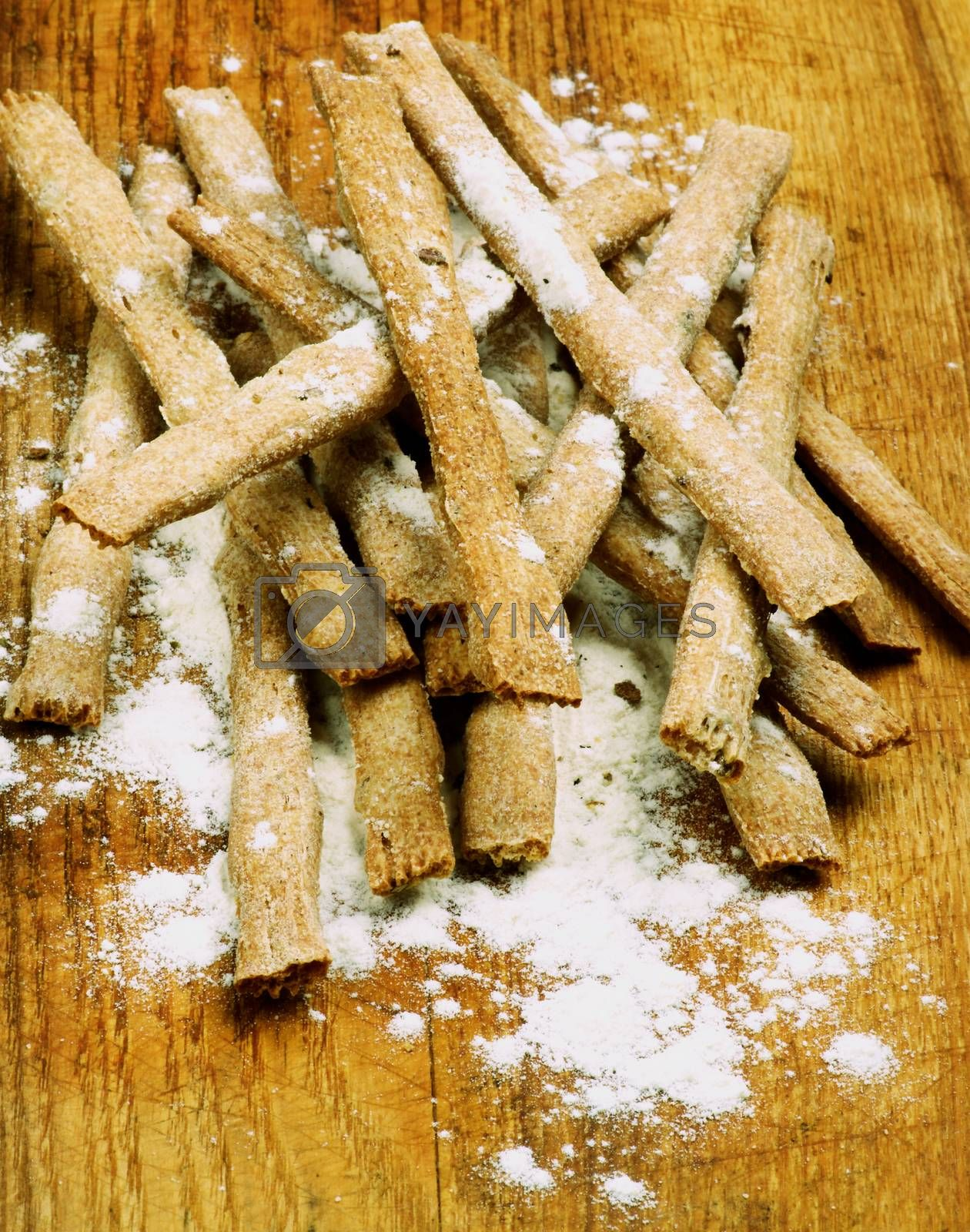 Stack of Freshly Baked Whole Wheat Bread Sticks with Dough closeup on Wooden Cutting Board