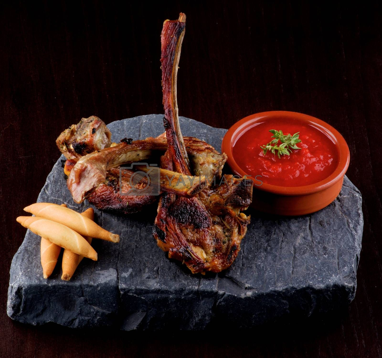 Delicious Roasted Lamb Ribs with Bread Sticks and Tomato Sauce on Stone Plate closeup on Dark Wooden background