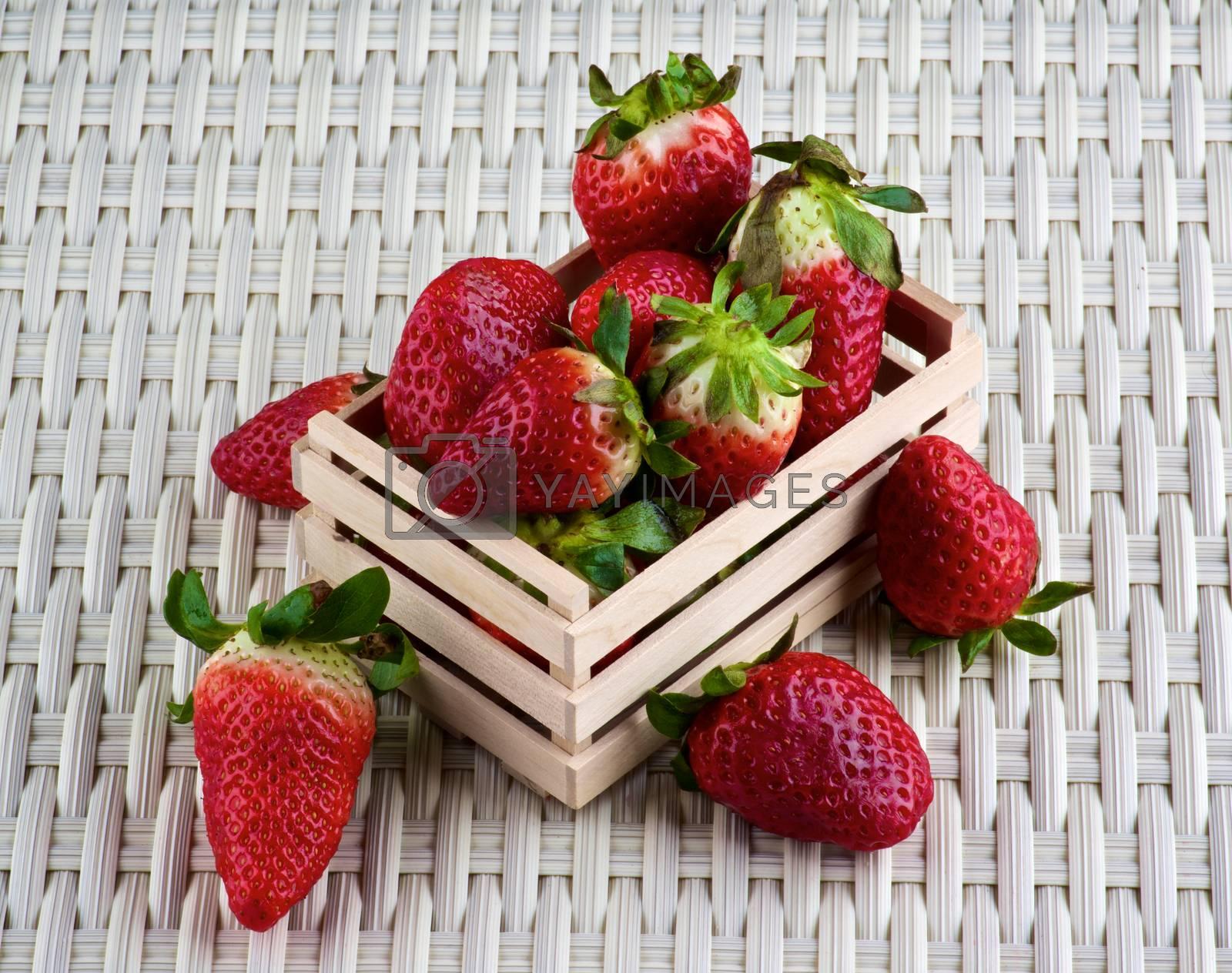 Arrangement of Fresh Ripe Strawberries in Wooden Tray closeup on Wicker background