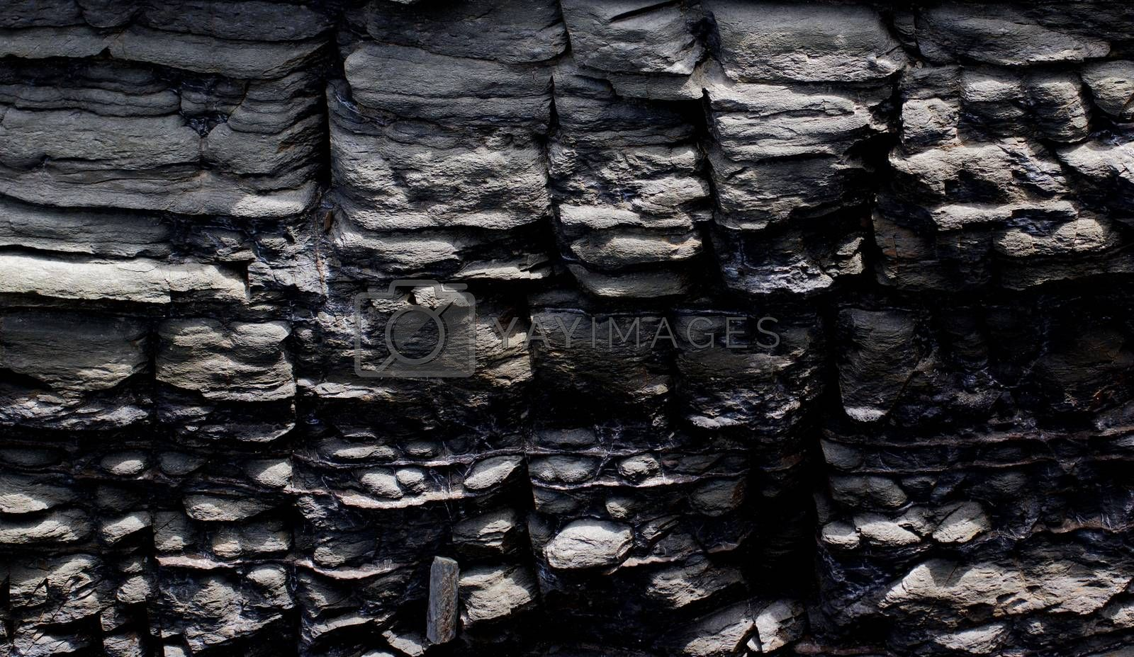 Background of Textured Dark Grey Shale Stone with Weathered Open-pit closeup Outdoors
