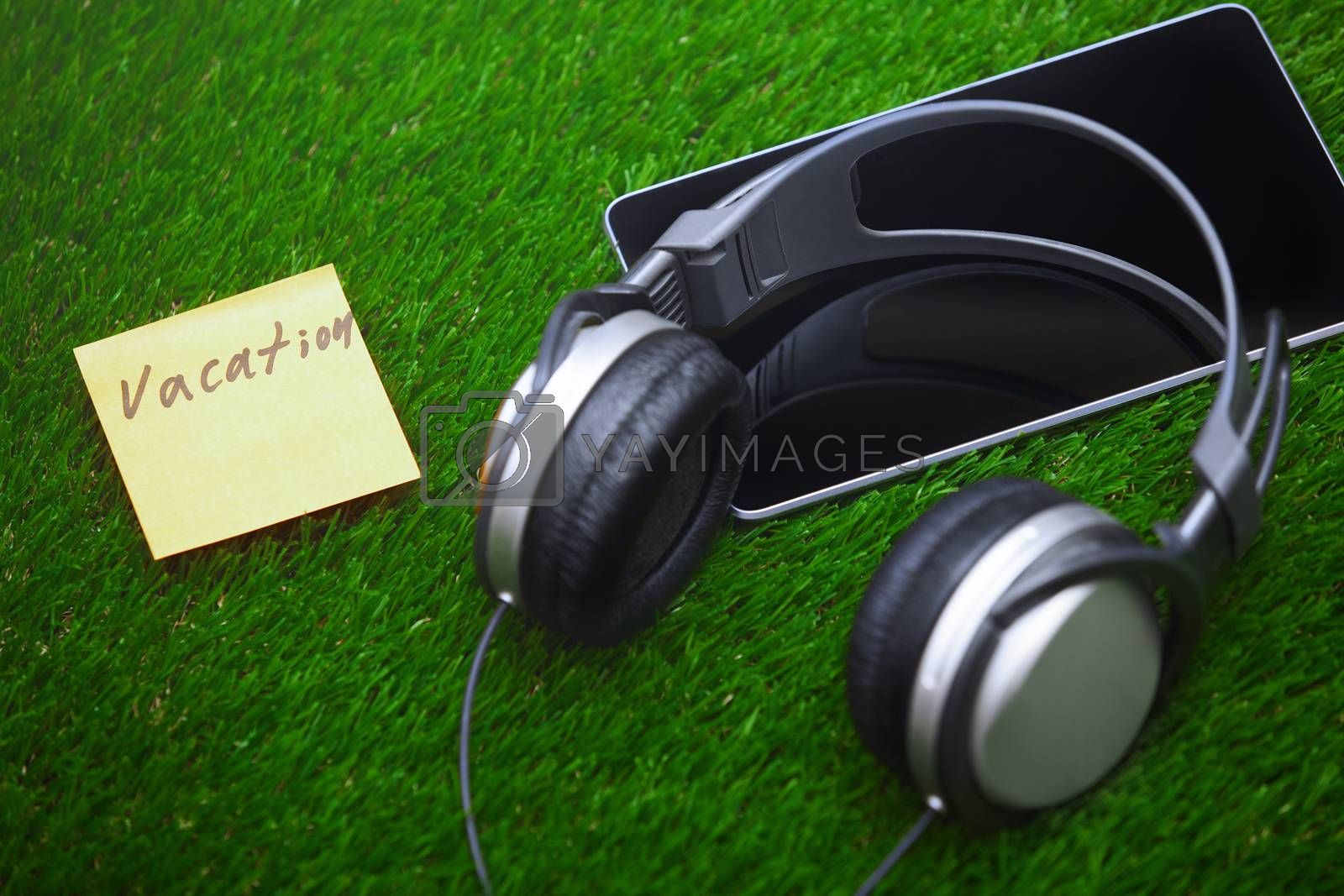Vacation text on sticky note on a grass with headphones and digital tablet