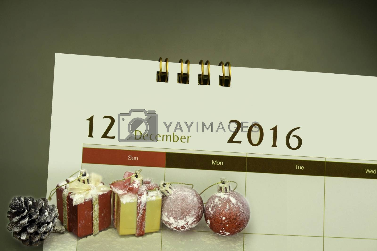 Christmas decorations and gift boxes with calendar page of month 2016