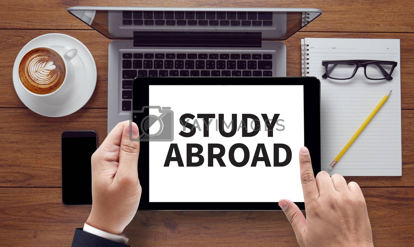 STUDY ABROAD, on the tablet pc screen held by businessman hands - online, top view