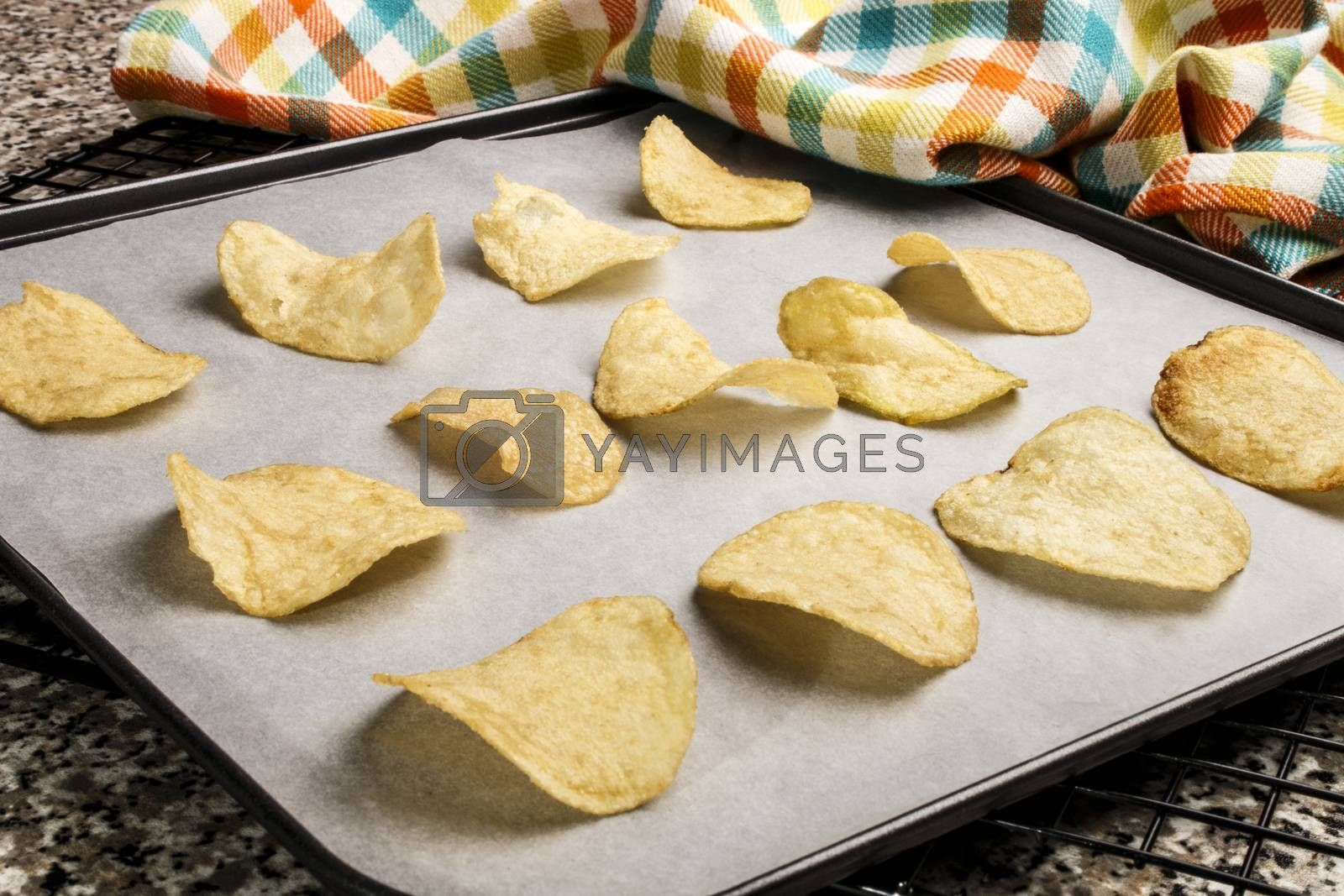 homemade potato chips on a baking tray with white paper