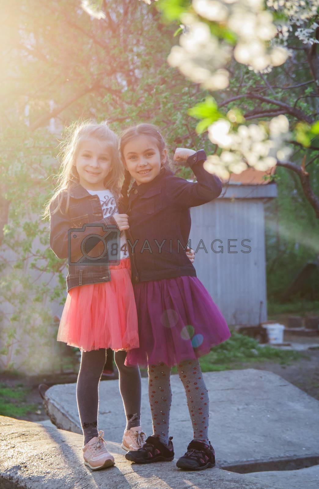 Two girls enjoying spring garden at sunset