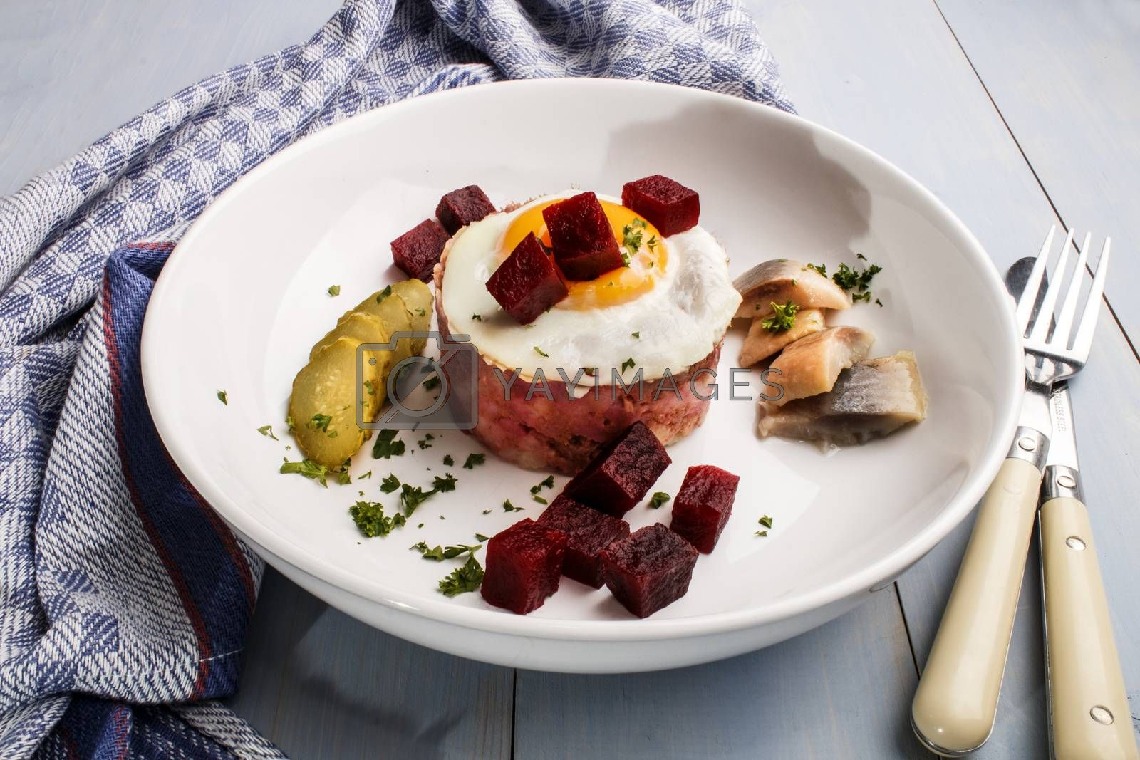 labskaus, north german specialty made with potatoes, beetroot, sour herring, gherkin slices, fried egg and parsley on a fine dining plate