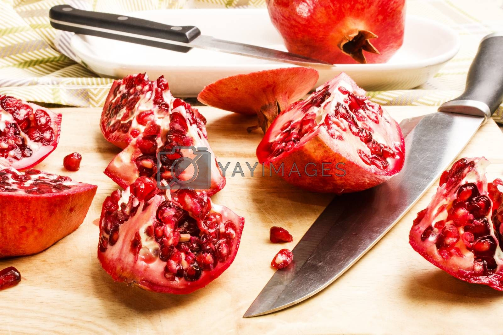 sliced organic pomegranate with knife on a wooden board
