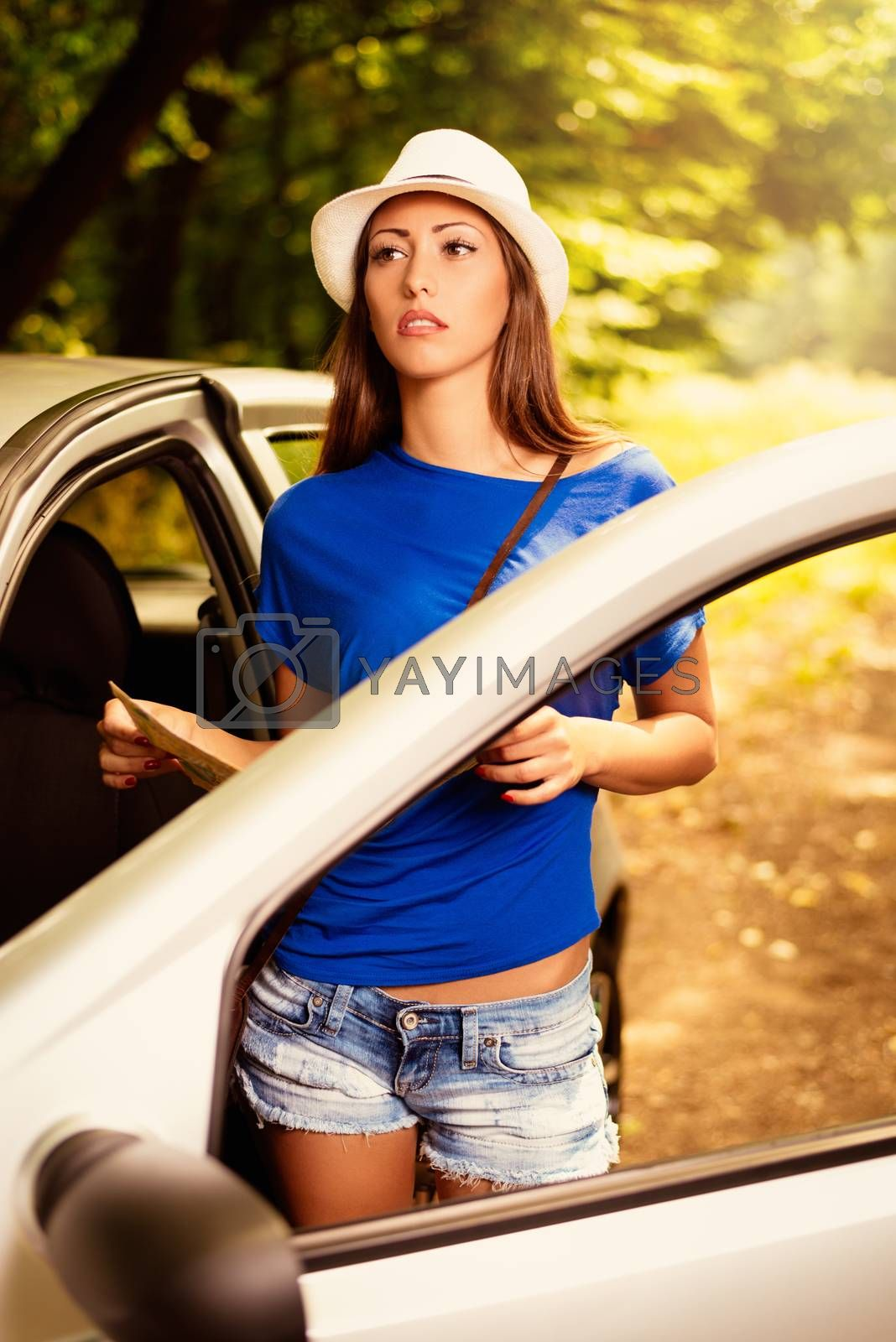 Confused pensive beautiful woman standing leaning at car in the forest and worried looking a map.