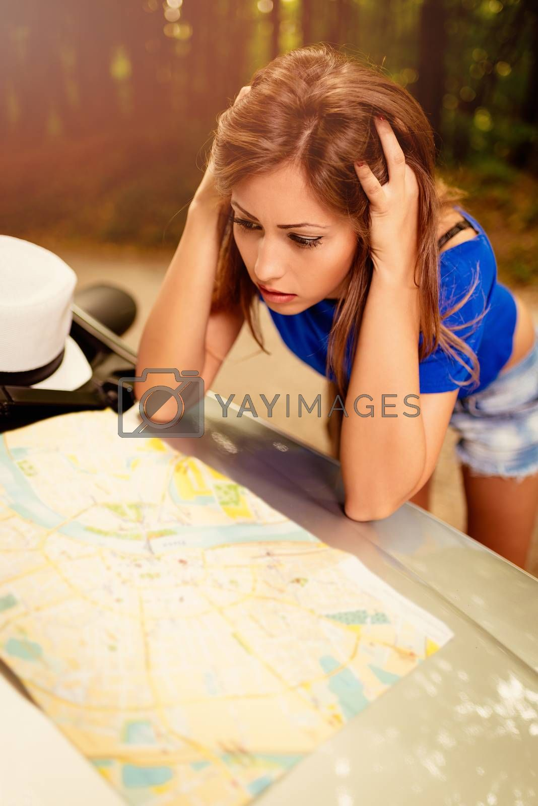 Confused lost beautiful woman standing leaning at car in the forest and worried looking a map.