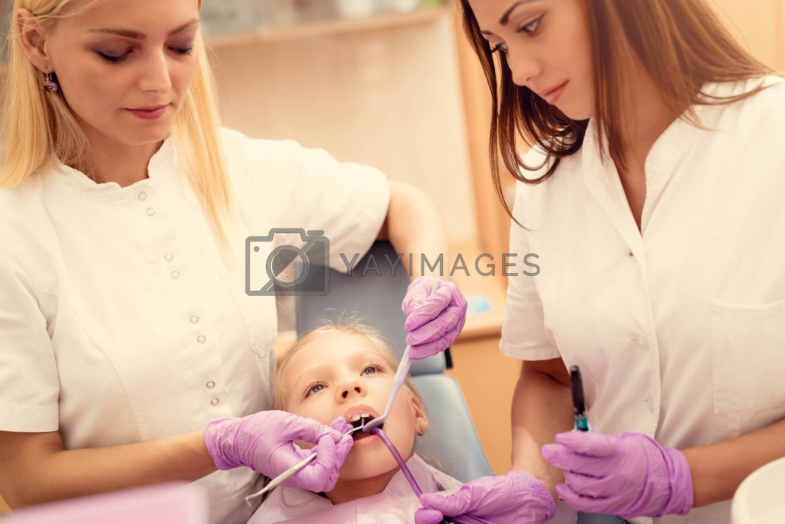 Beautiful little girl at visit in the dentist office. She is sitting on a chair and female dentist checkup teeth on her. Selective focus.