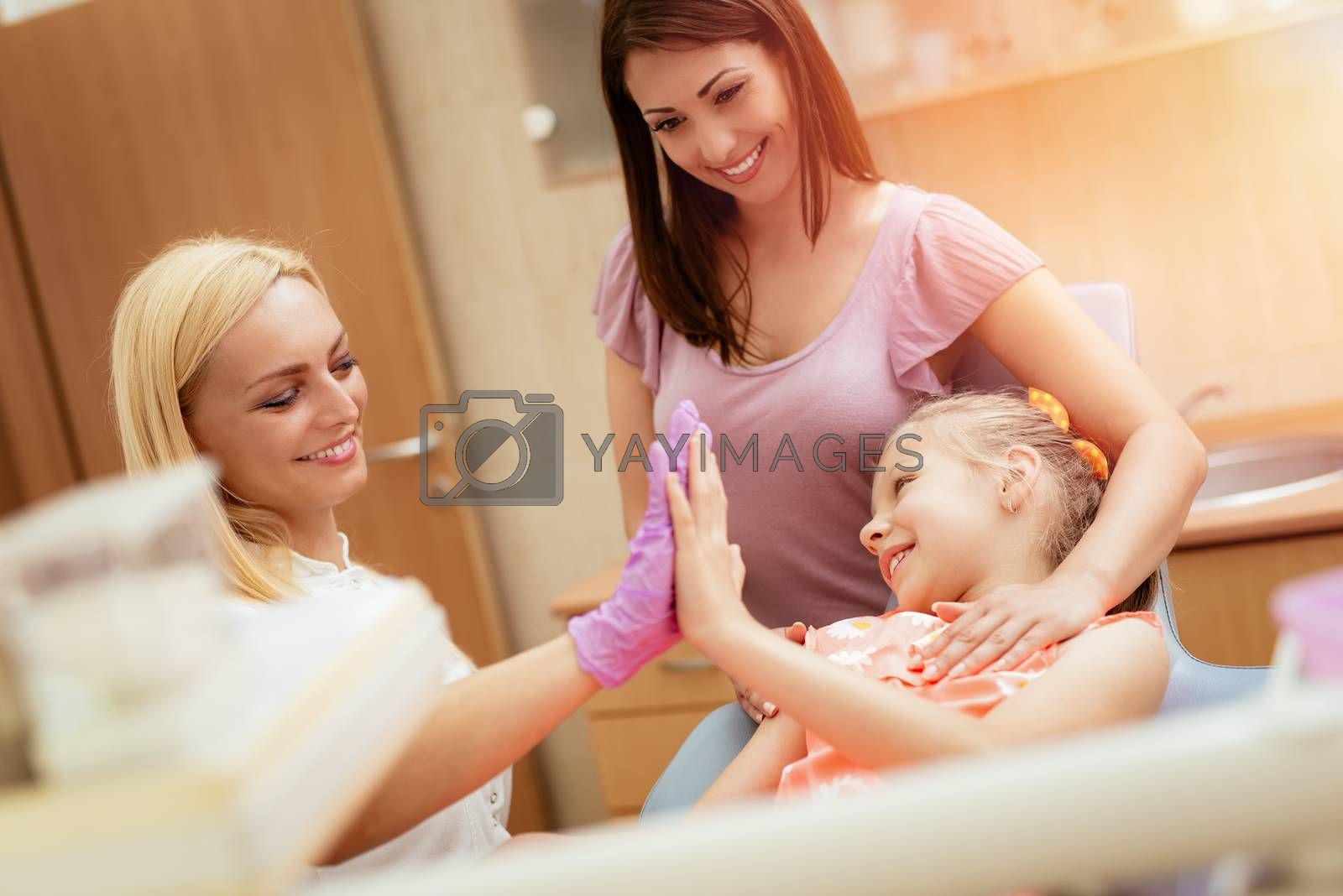 Beautiful little girl at visit in the dentist office. She and female dentist greeting and having fun.