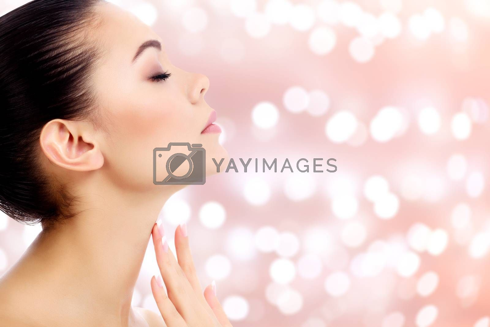 Young female touches her neck on an abstract background with blurred lights