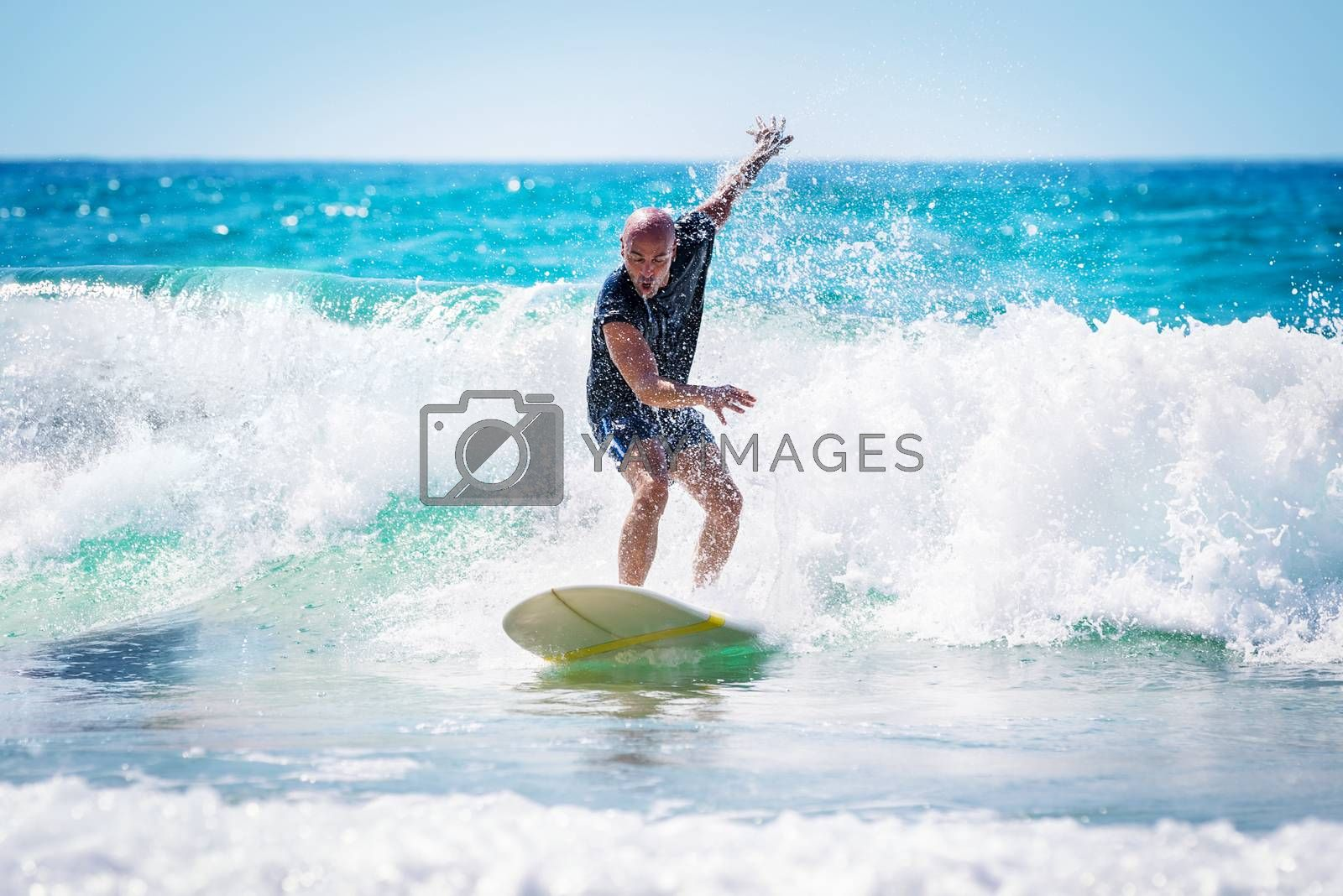 Surfer enjoying high waves in bright sunny day, active lifestyle, extreme water sport, summer time activities, recreation on the beach