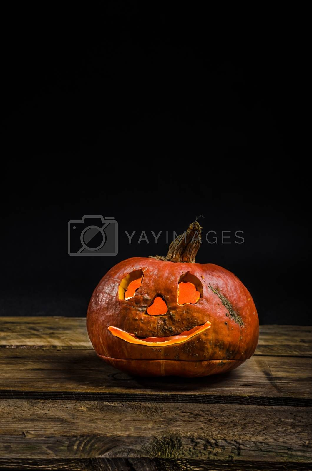 Halloween pumpkin, black background, simple picture on wood table