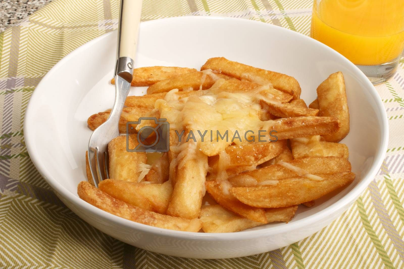 french fries with melted irish cheddar cheese and orange juice in a glass