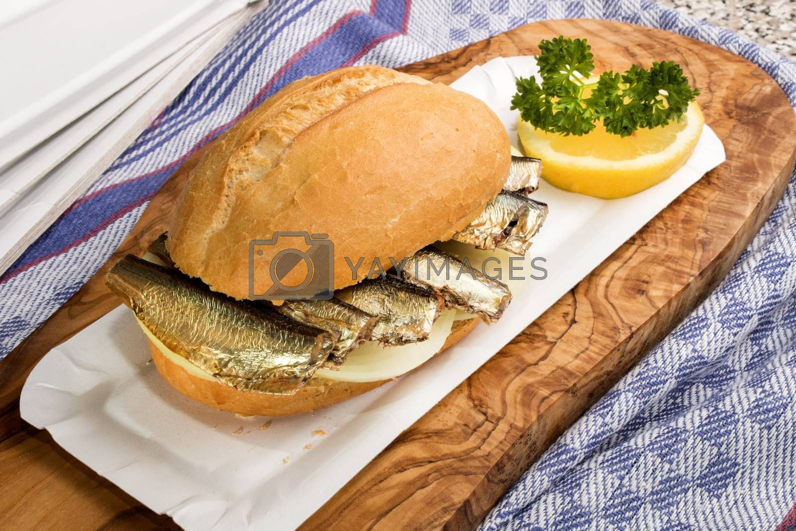 smoked sprats on a bread roll and slice onion, lemon with parsley
