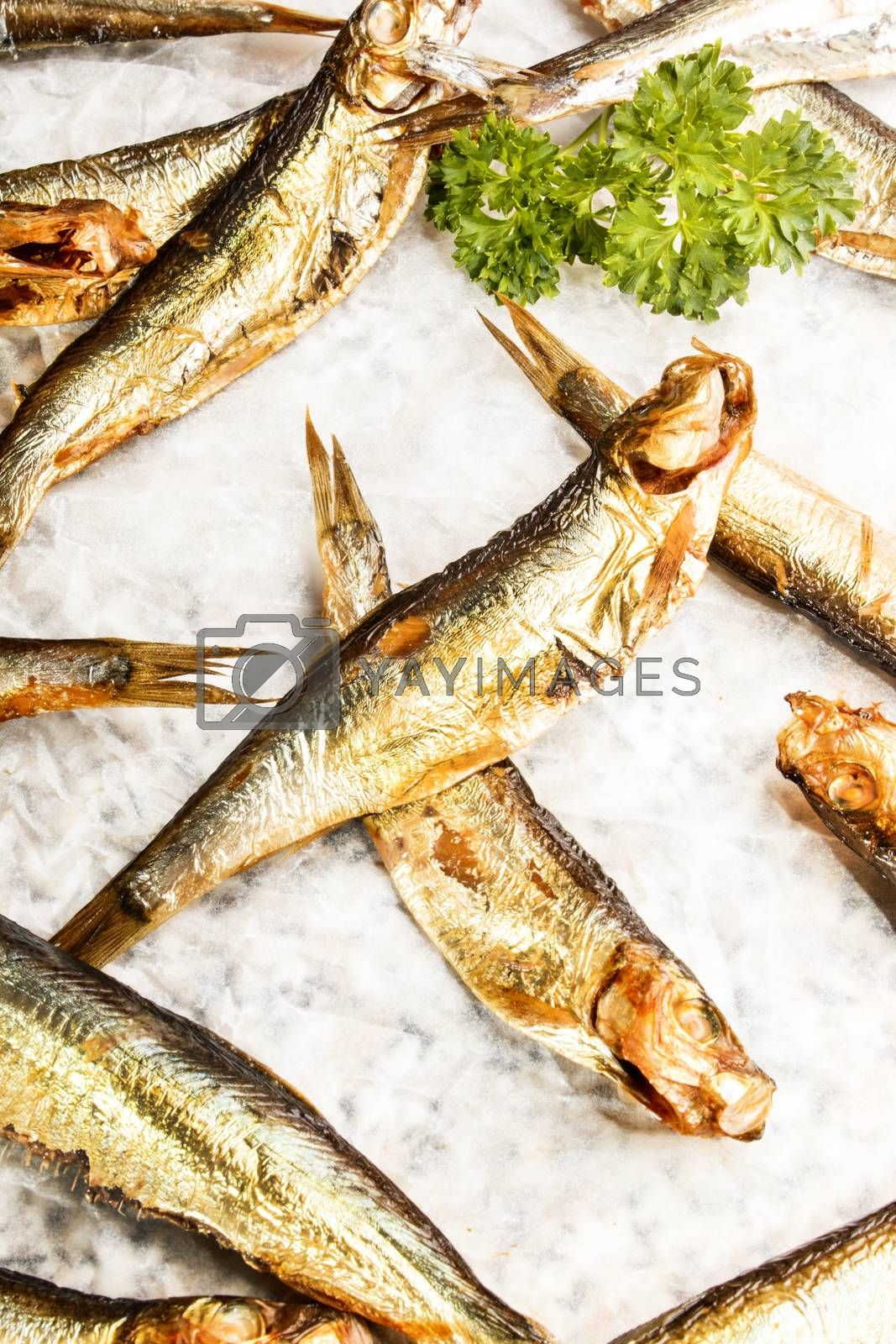 some smoked sprats and parsley on white paper
