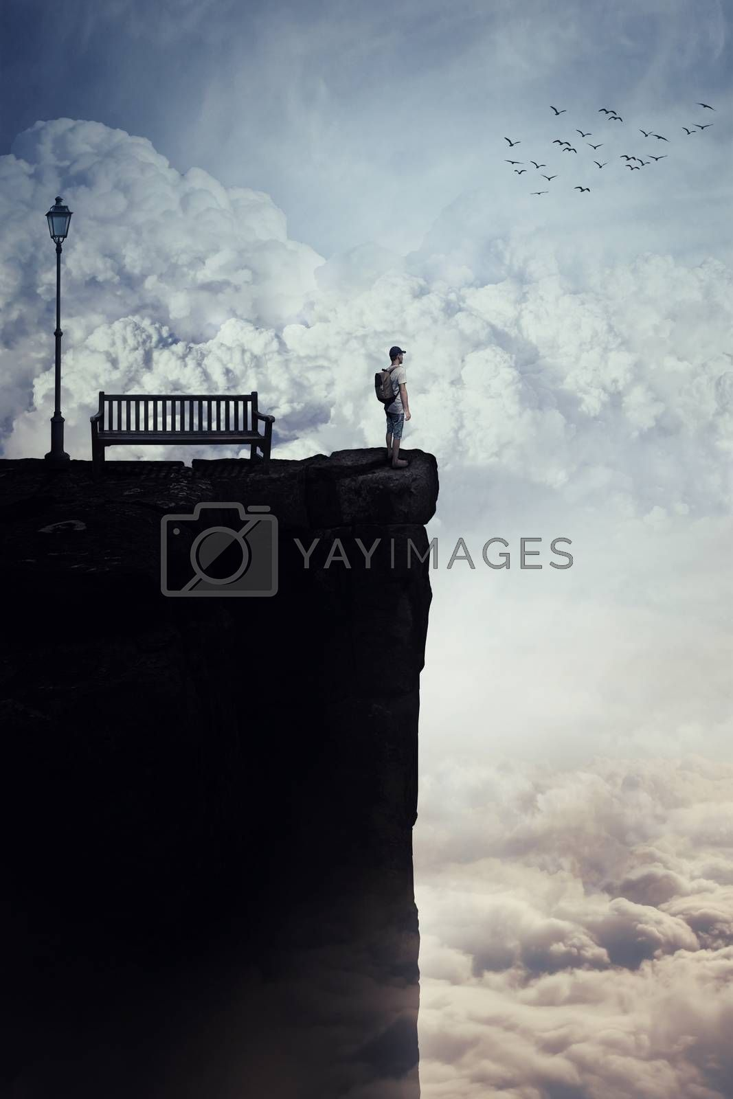 Inspirational imaginary view as a young boy with a bag in his back stand on the peak of a cliff above clouds, looking at the horizon, near a bench and a street lamp. Life journey opportunity concept.