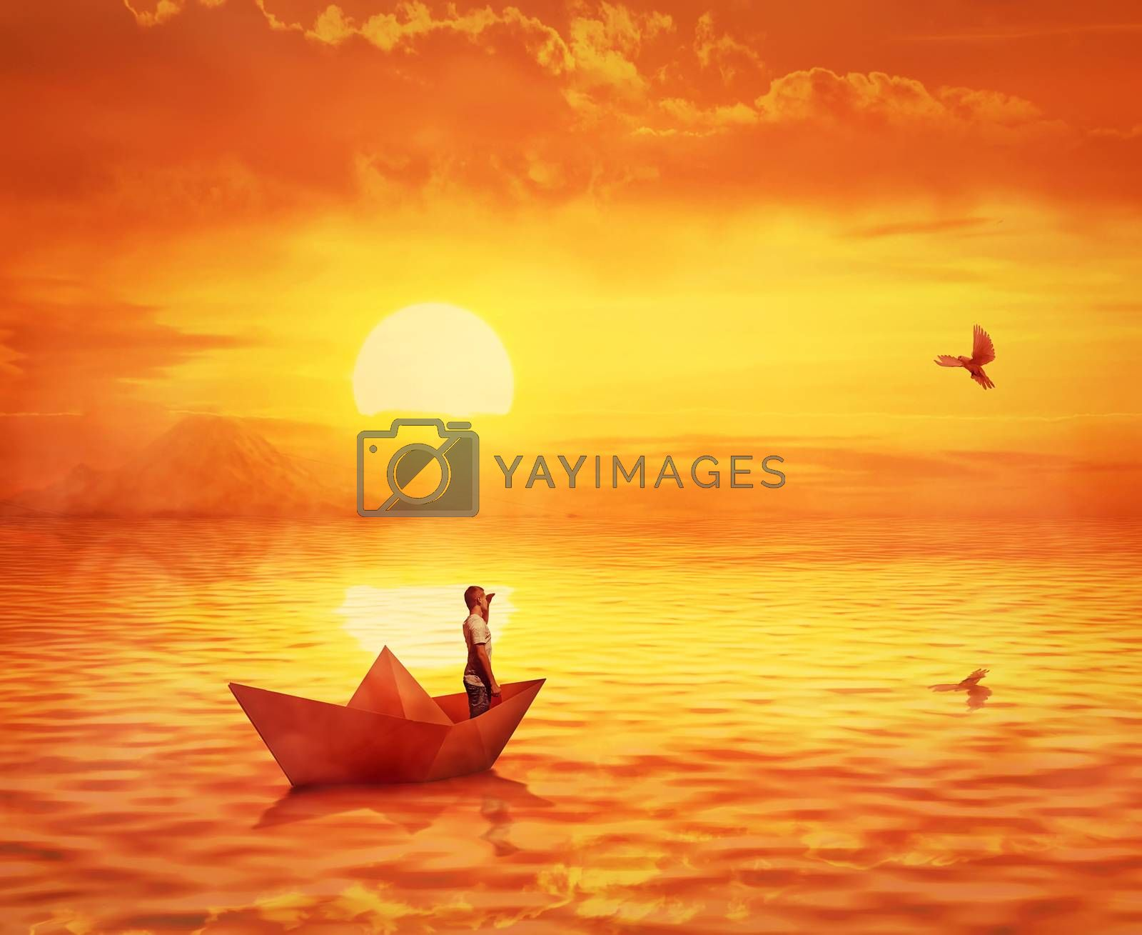 Silhouette of a lonely boy in a paper boat sailing lost in the ocean, against orange sunset sky and a pigeon flying to find the shore. Adventure and journey concept, searching for help.