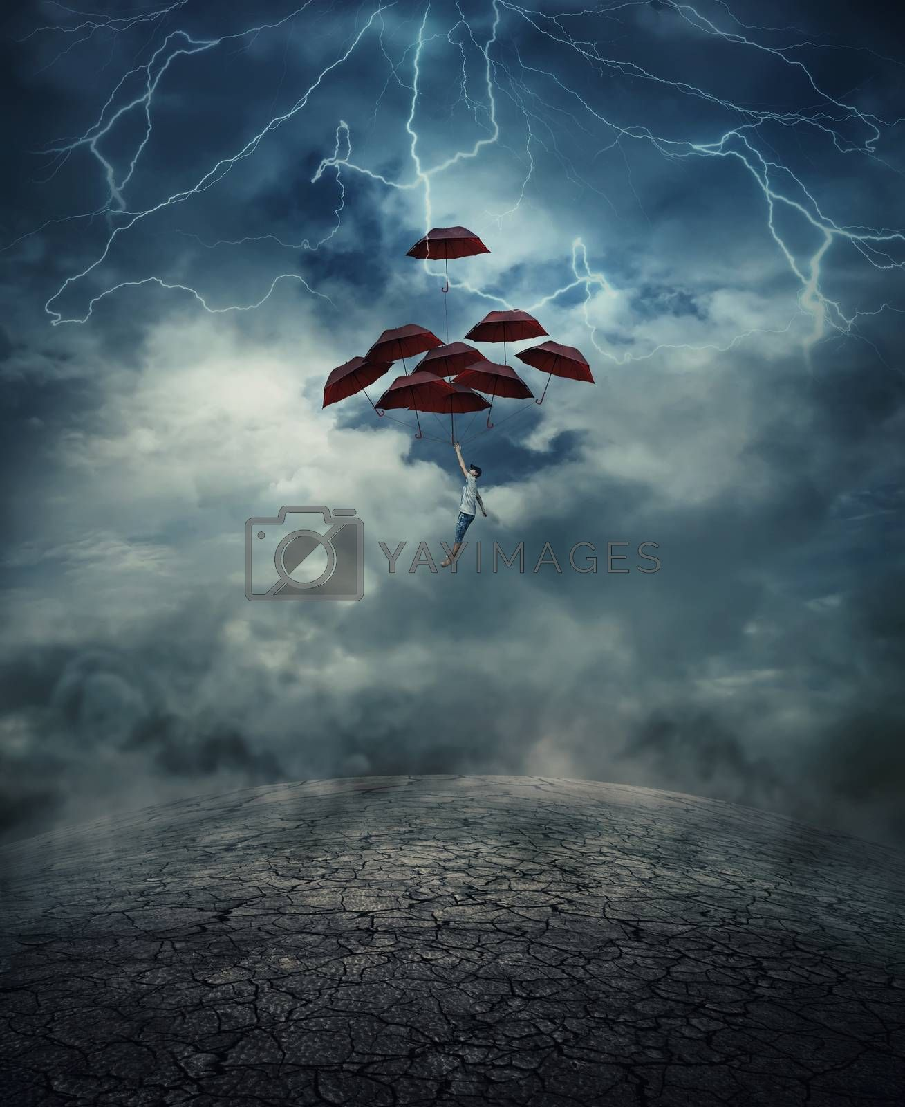 Young man with a lot of umbrellas as an air balloon rise up to the sky full of lightnings, above the cracked desert ground. Risk and success concept.