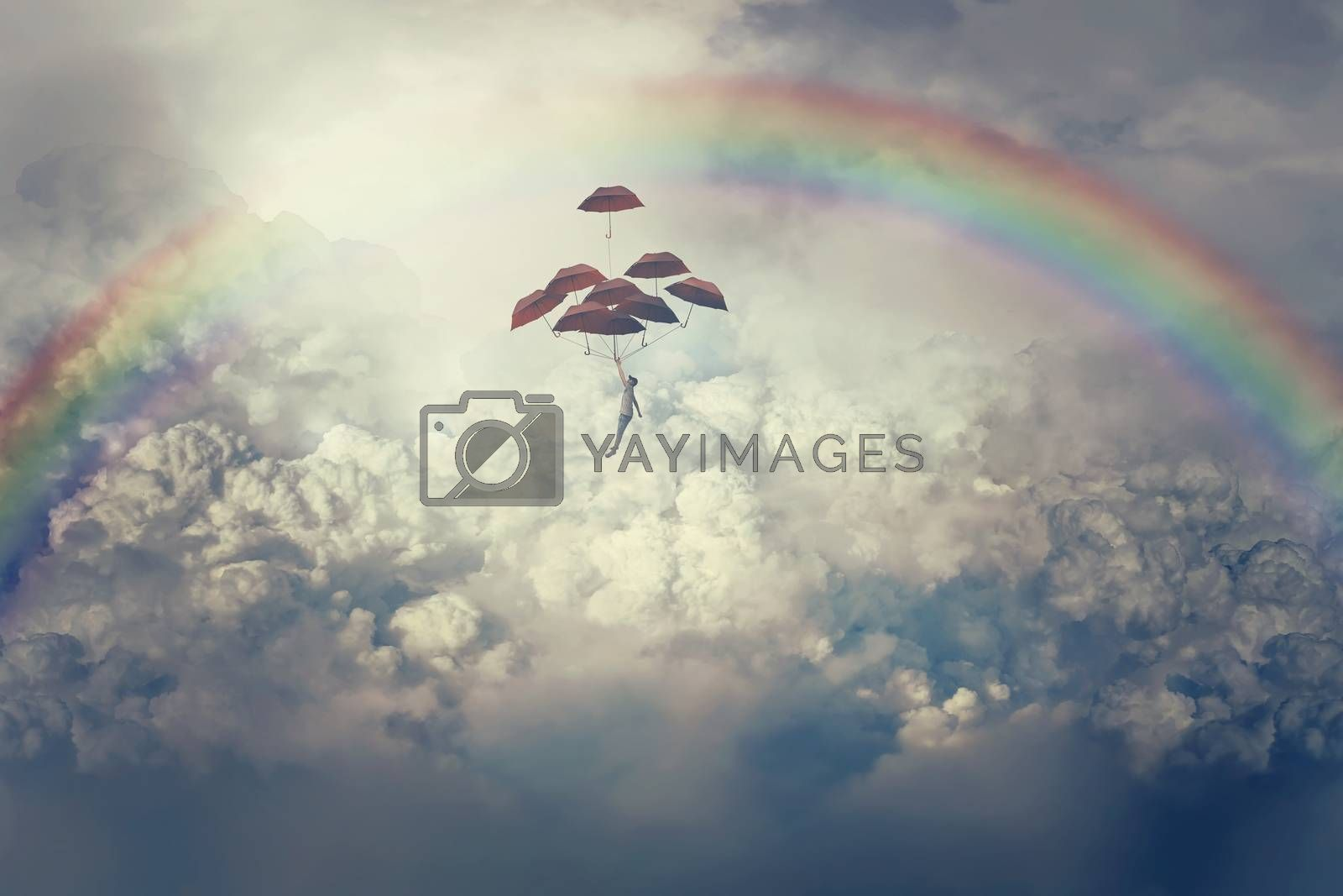 Imaginary view with a young boy flying above clouds holding a lot of umbrellas. Life journey below a rainbow in the sky.