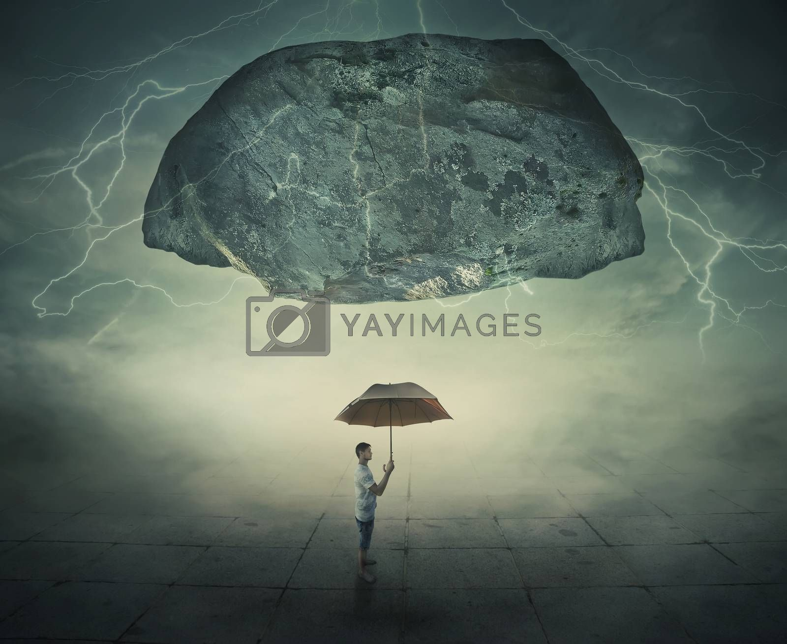 Surrealistic image as a man stand in a foggy street under a huge levitating rock, holding an umbrella in hand as a protection from danger. Life pressure and stress concept.
