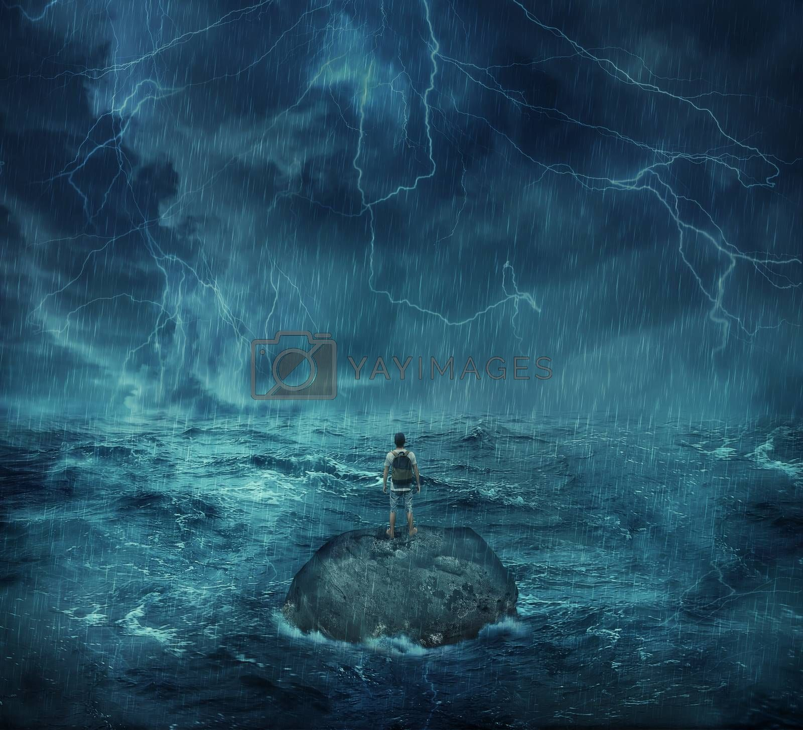 Lost man standing abandoned on a rock island in middle of the ocean, in a stormy night with lightnings in the sky. Looking for help, trying to survive. Adventure, journey and hard determination concept.