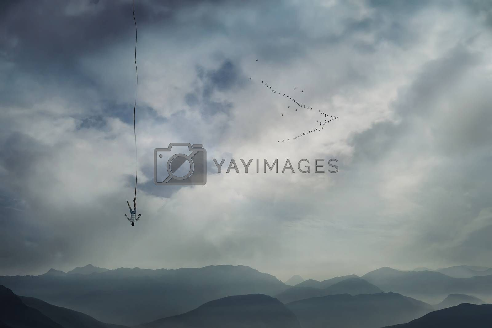 Young man falling from the sky with a rope tied to his leg as safety insurance. Base jump, mysterious crash, life risk and hard determination concept.
