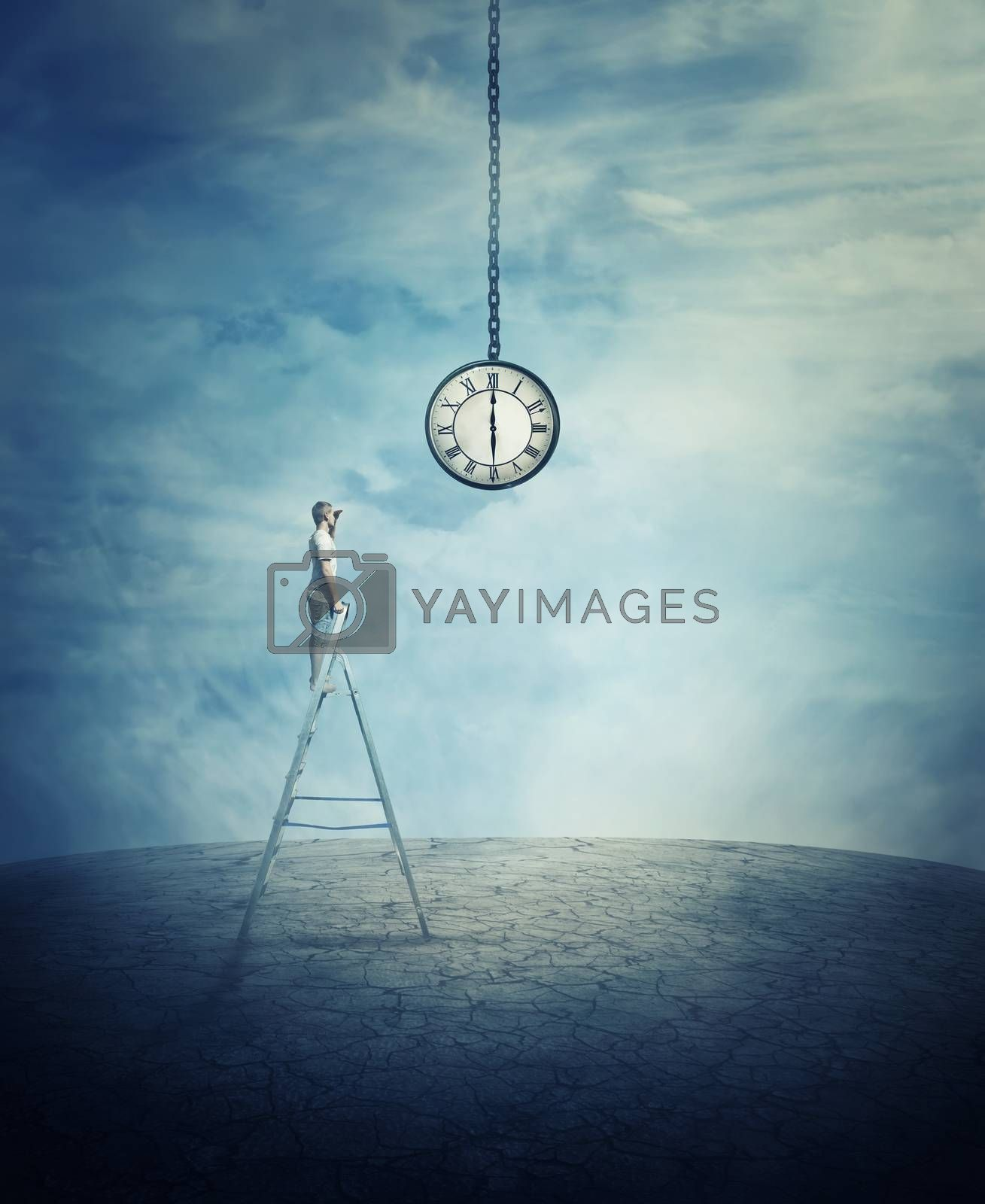 Young boy stay on the top of a ladder in the middle of a cracked desert ground, looking at a huge suspended clock.