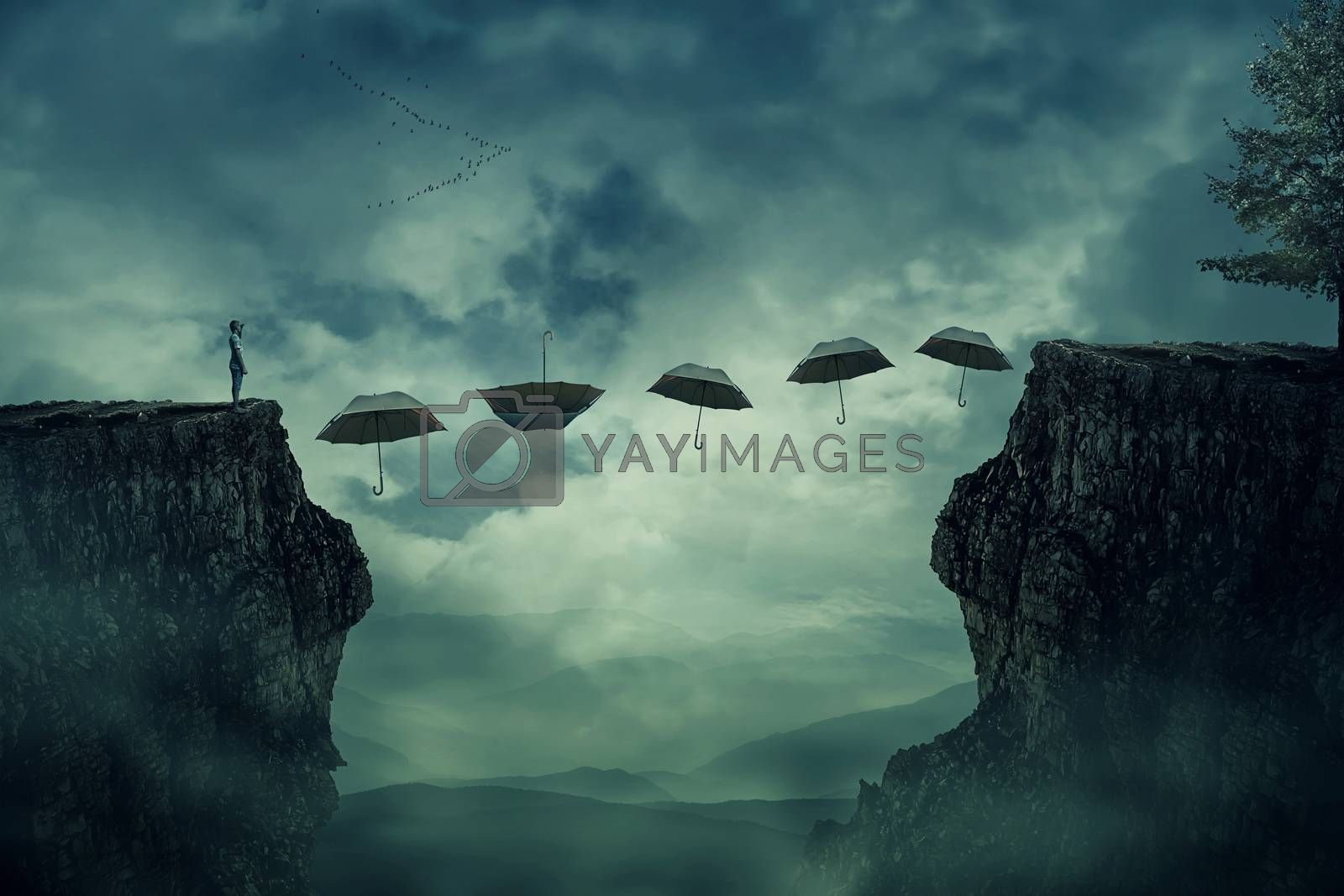 Young boy standing on the peak of a cliff try to pass over valley to another side on a path way of flying umbrellas. The pursuit of happiness and success concept.