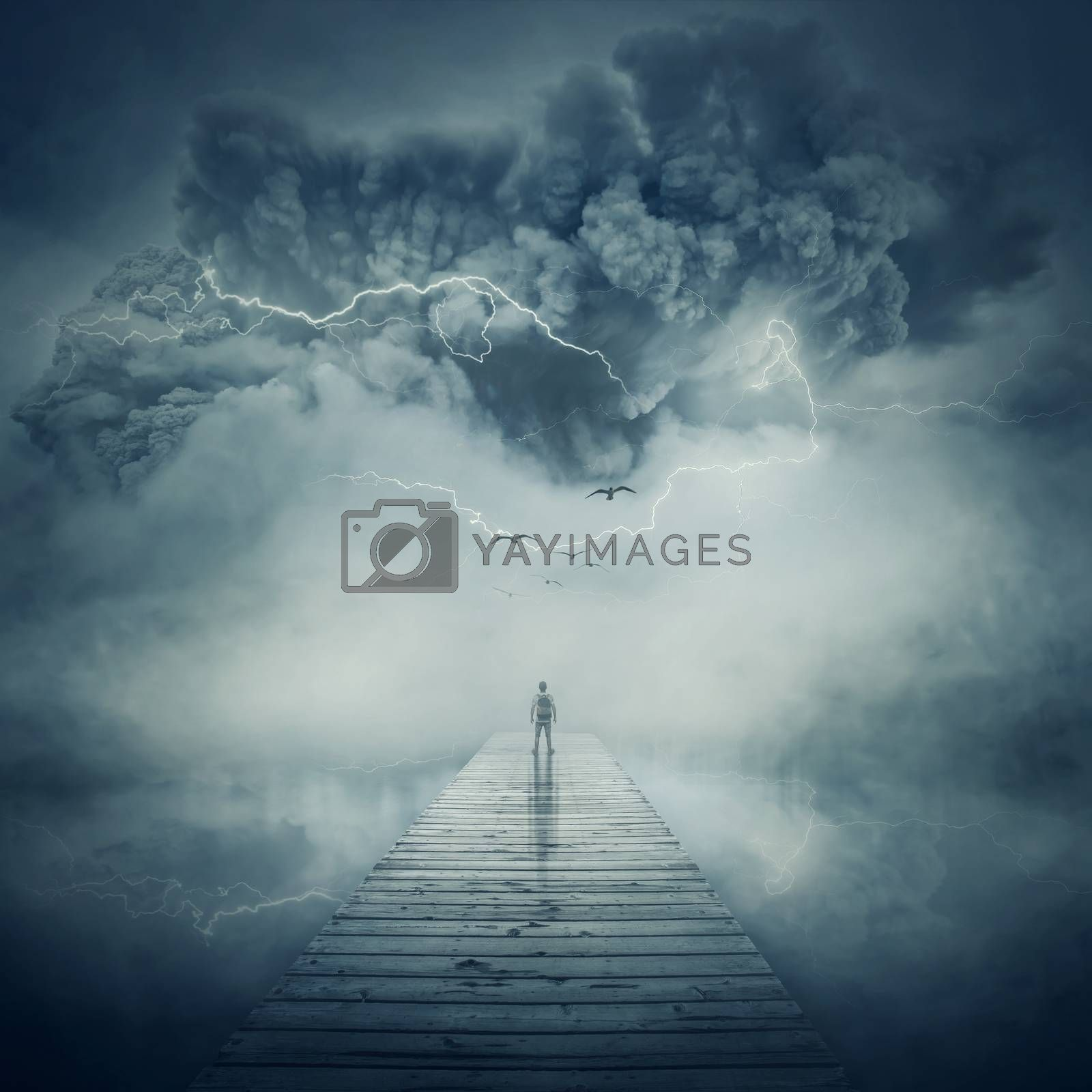 Fantastic view as a man, stand on the wooden pier at the middle of the lake in a foggy and stormy day watching a hurricane coming. Facing the life pressure and stress concept.