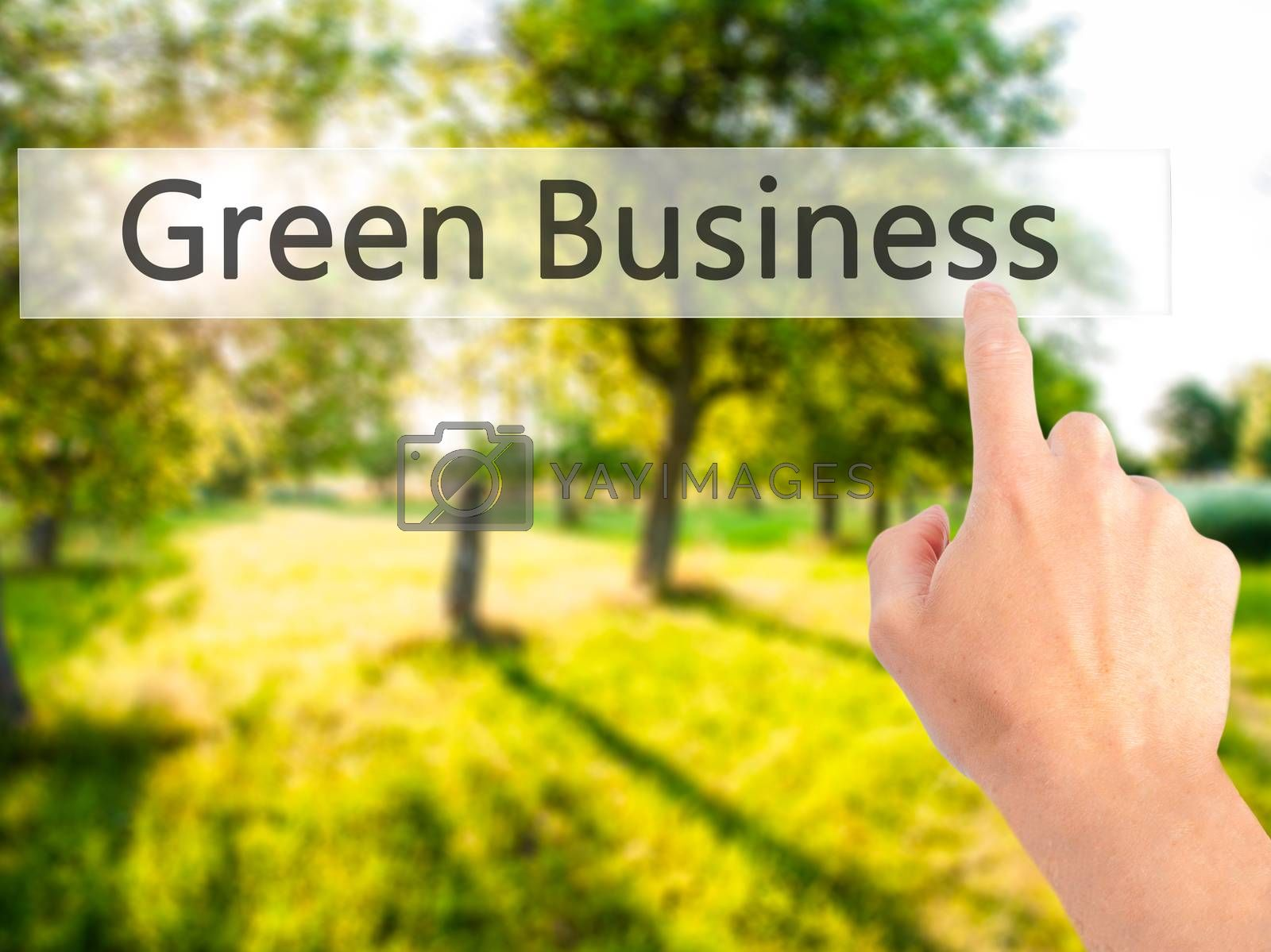 Green Business  - Hand pressing a button on blurred background c by jackald