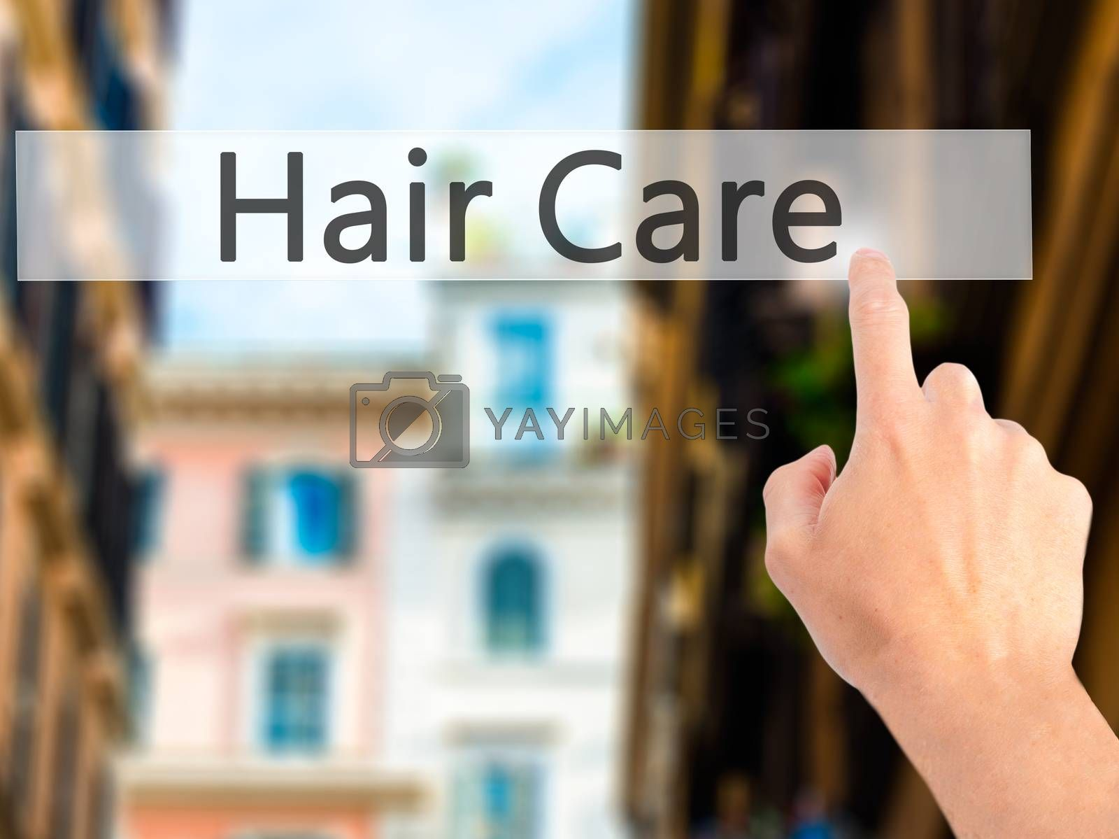 Hair Care - Hand pressing a button on blurred background concept by netsay.net